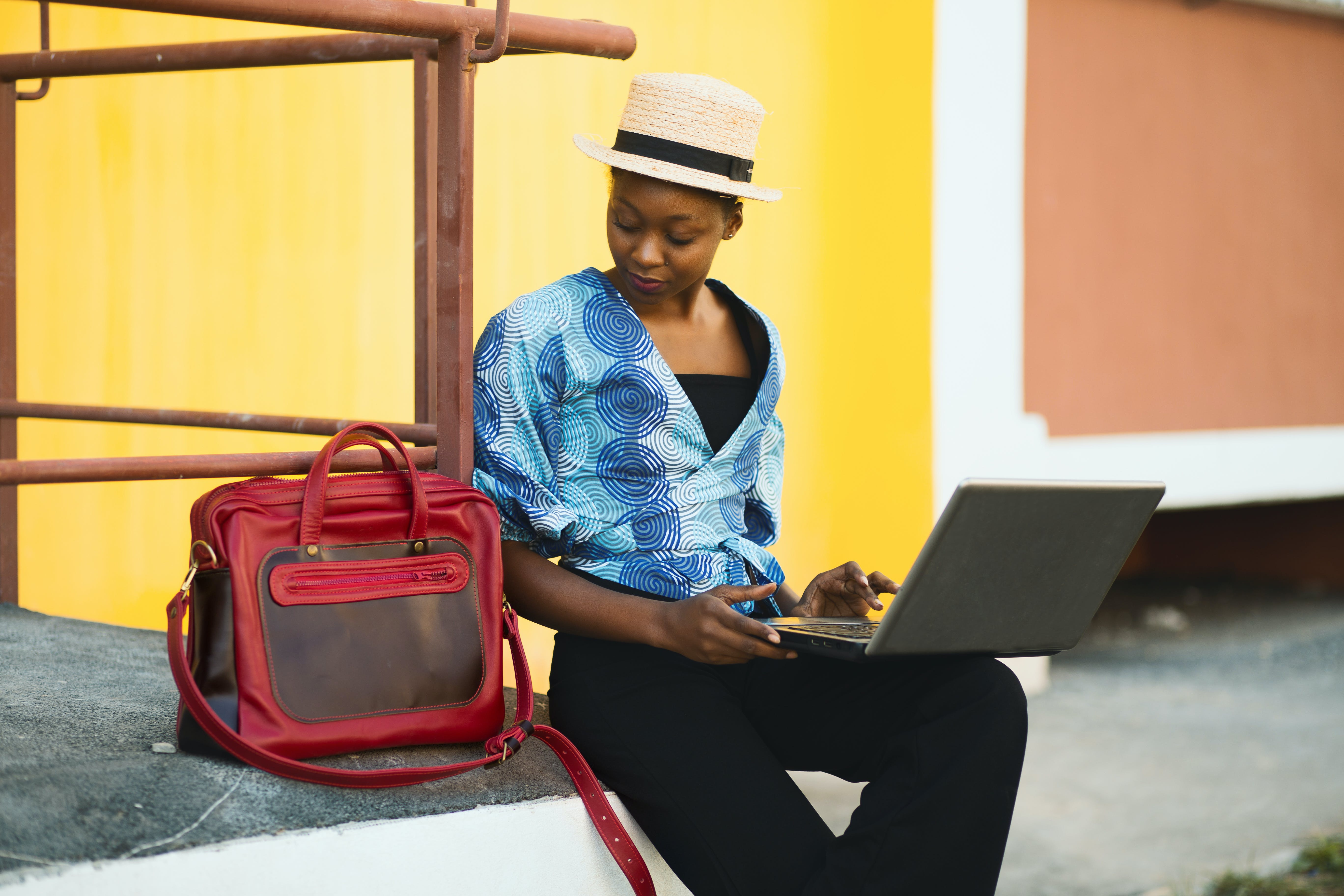 Woman Sitting Beside Bag And Using Laptop