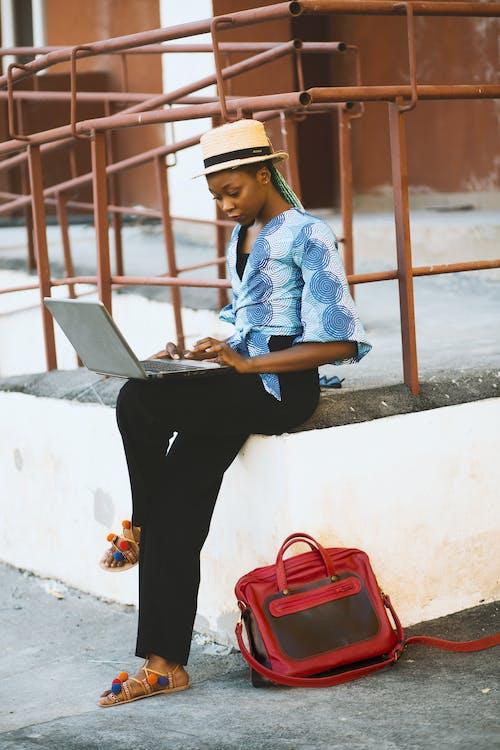 Woman Sitting on White Concrete Edge With Railing