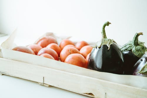 Close-up Photo of Purple Eggplants and Round Orange Fruits
