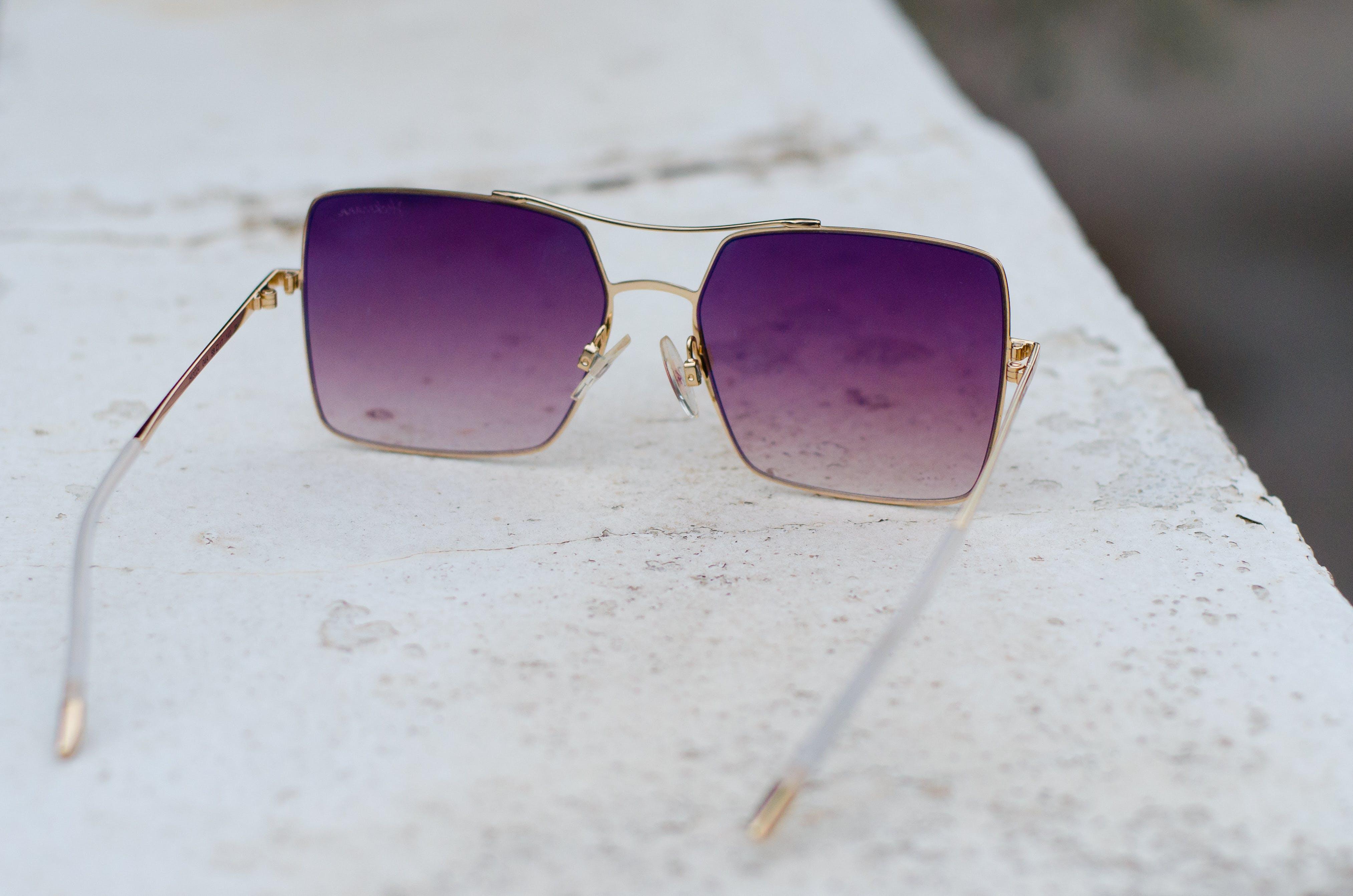 Gold-colored Framed Purple Lens Sunglasses on Gray Surface