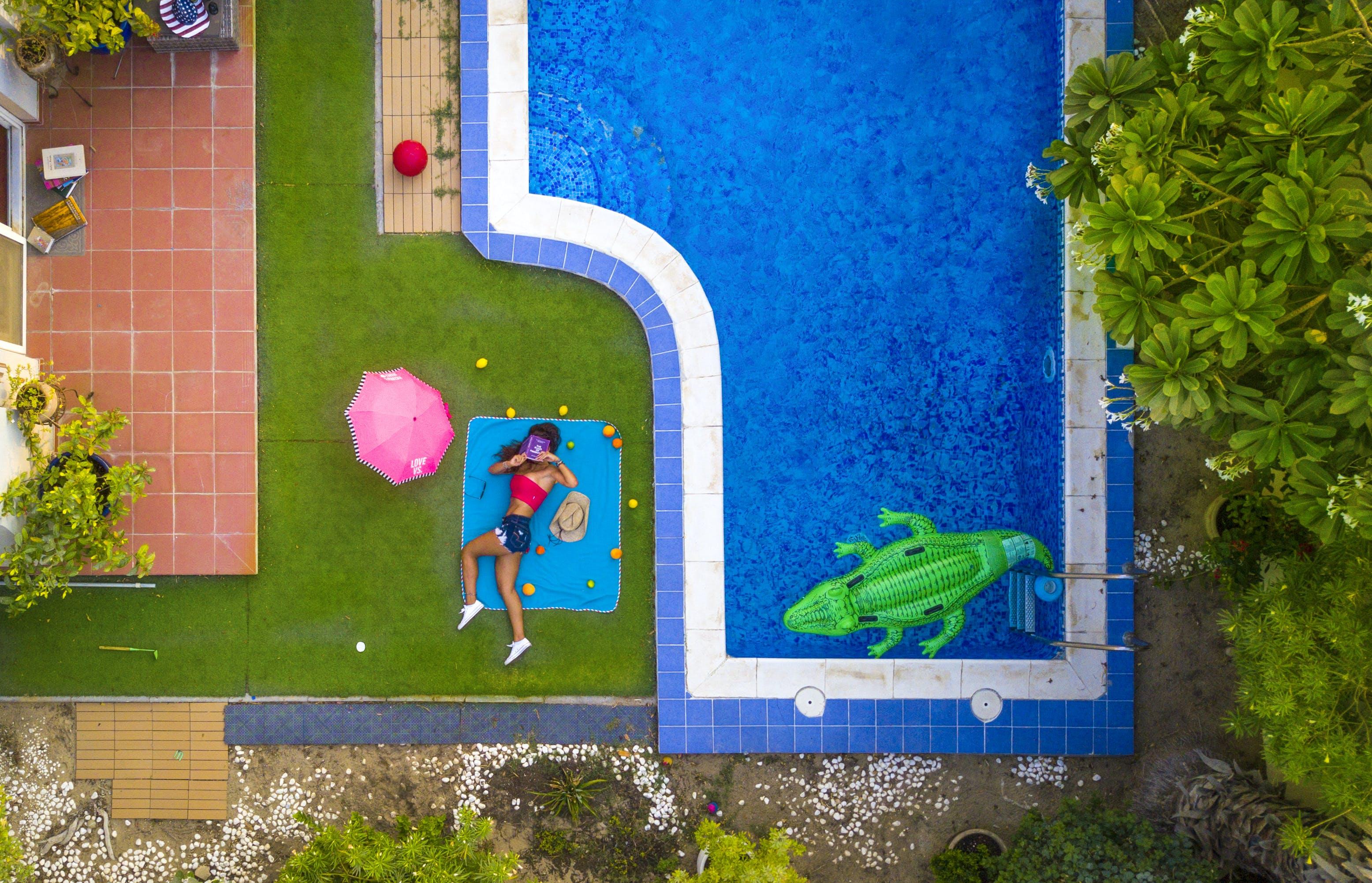 Woman Lying on Blue Mat Beside a Pool