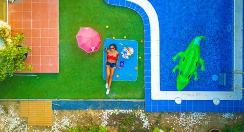 Slim female tourist sunbathing near bright swimming pool on vacation