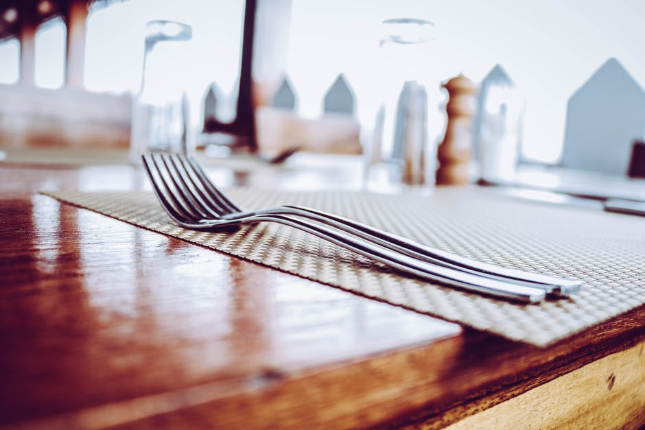 Two stainless steel forks on top of place mat