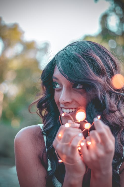 Selective Focus Photo of Woman Holding String Lights While Smiling