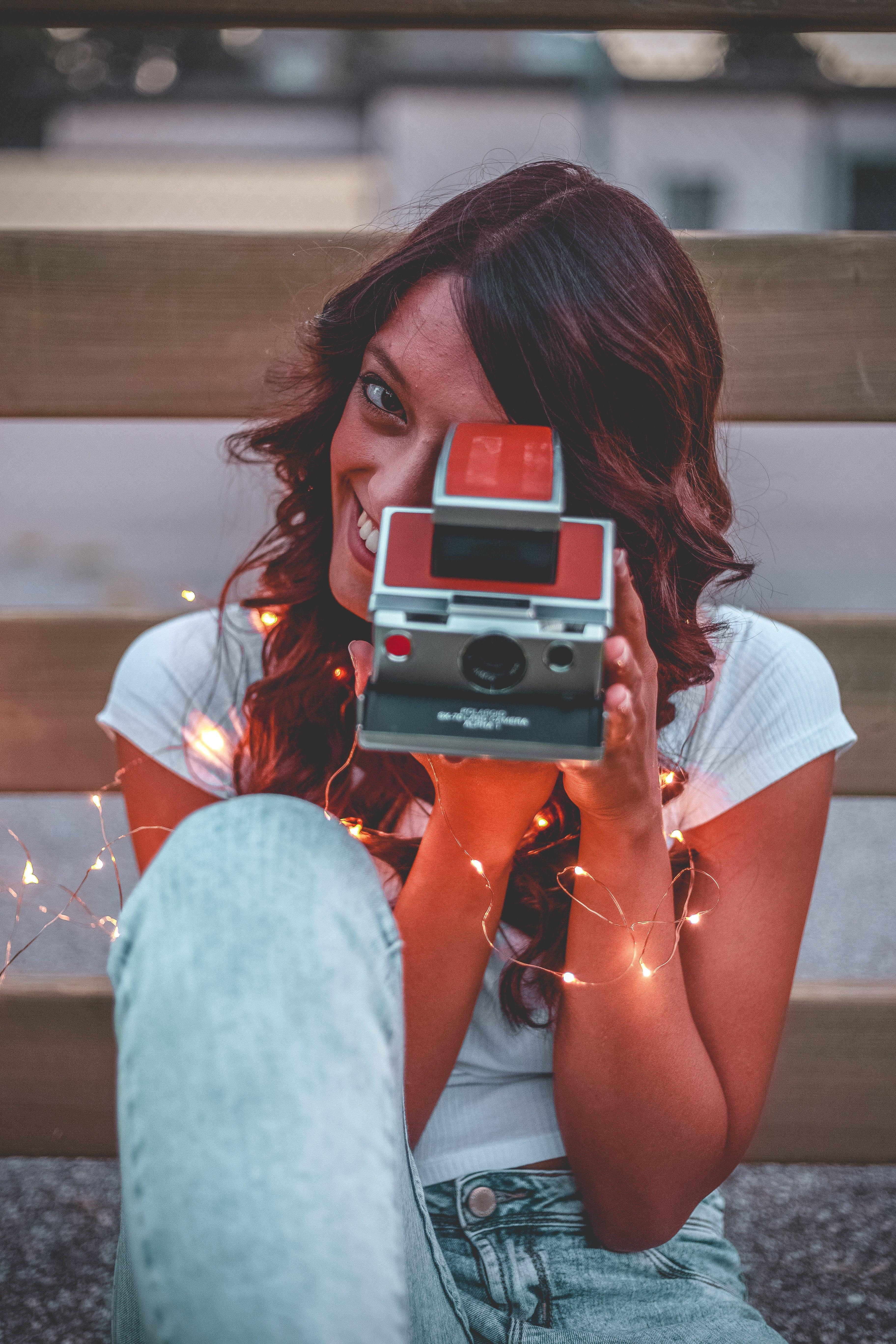 Foto profissional grátis de câmera, câmera instantânea, cordão de lâmpadas, fotografando
