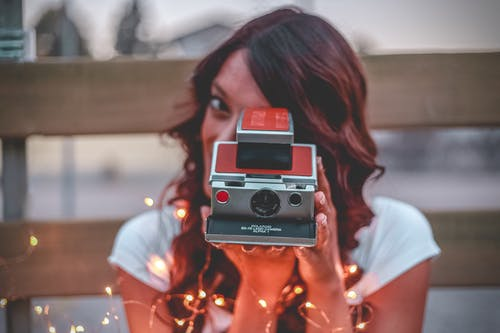 Woman Holding Red And Grey Camera i