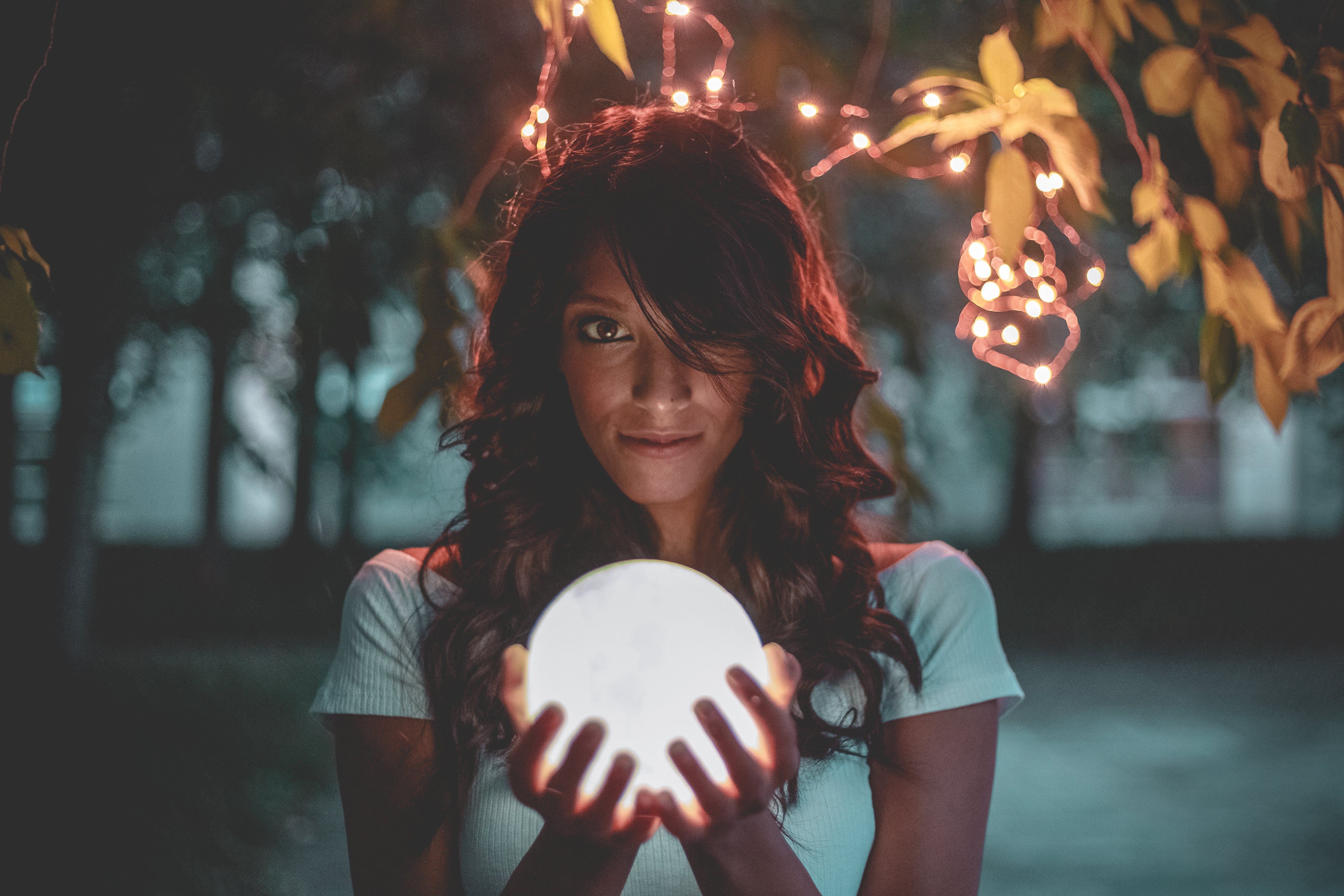 Woman Holding Lighted Glass Ball Under String Lights