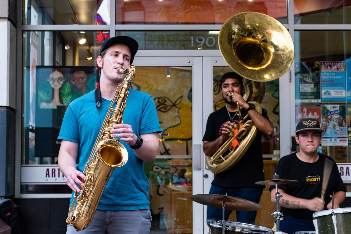 Three Man Playing Drums And Wind Instruments In Front Of Store