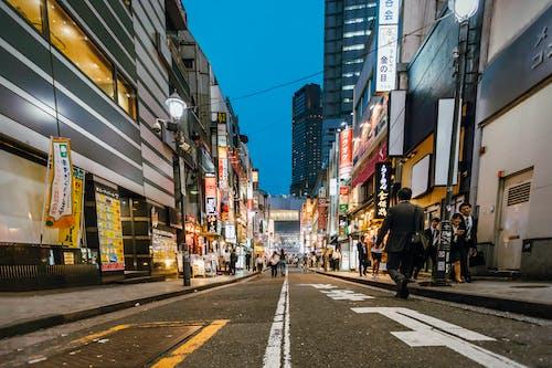 People Walking Between High-rise Buildings