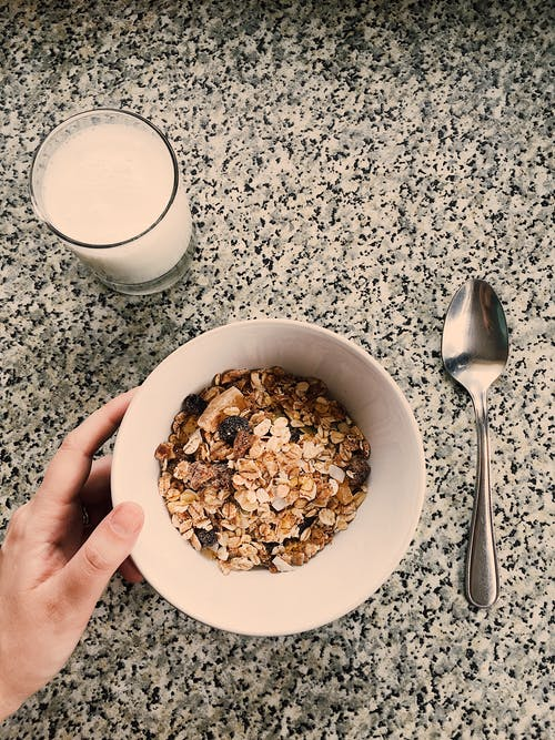 Round White Ceramic Bowl Filled With Oatmeal Beside Glass Of Milk