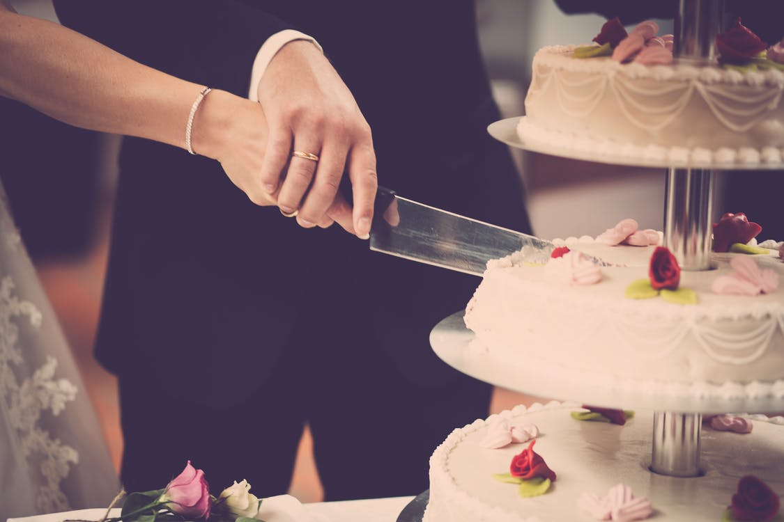 Person Holding Knife Slicing 3-layer Cake