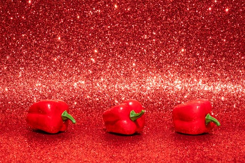 Three Red Bell Peppers on Red Surface