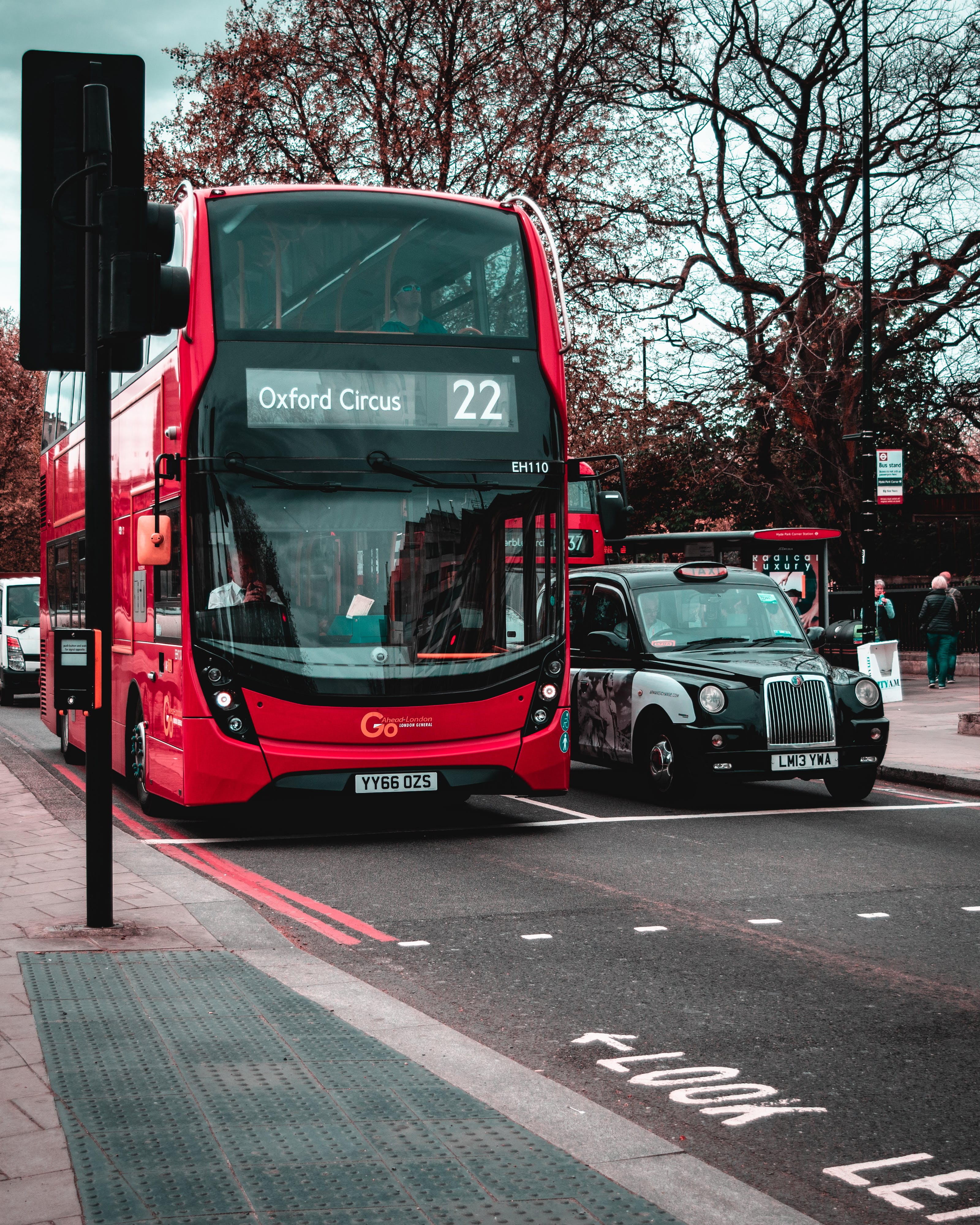 Red Double-Decker Bus Beside Black Taxi Cab On Asphalt Road