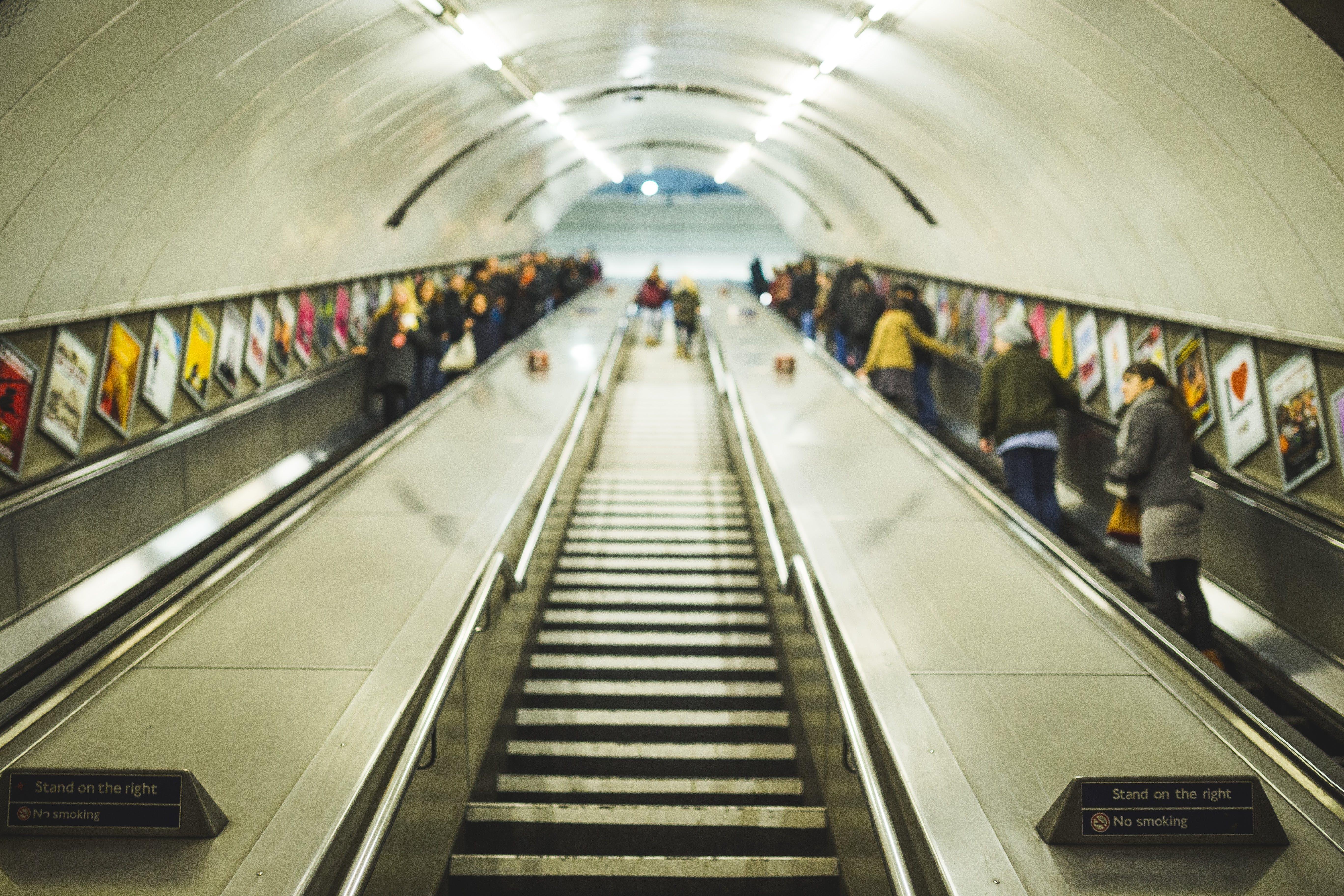 People Standing on Escalators Inside Tunnel
