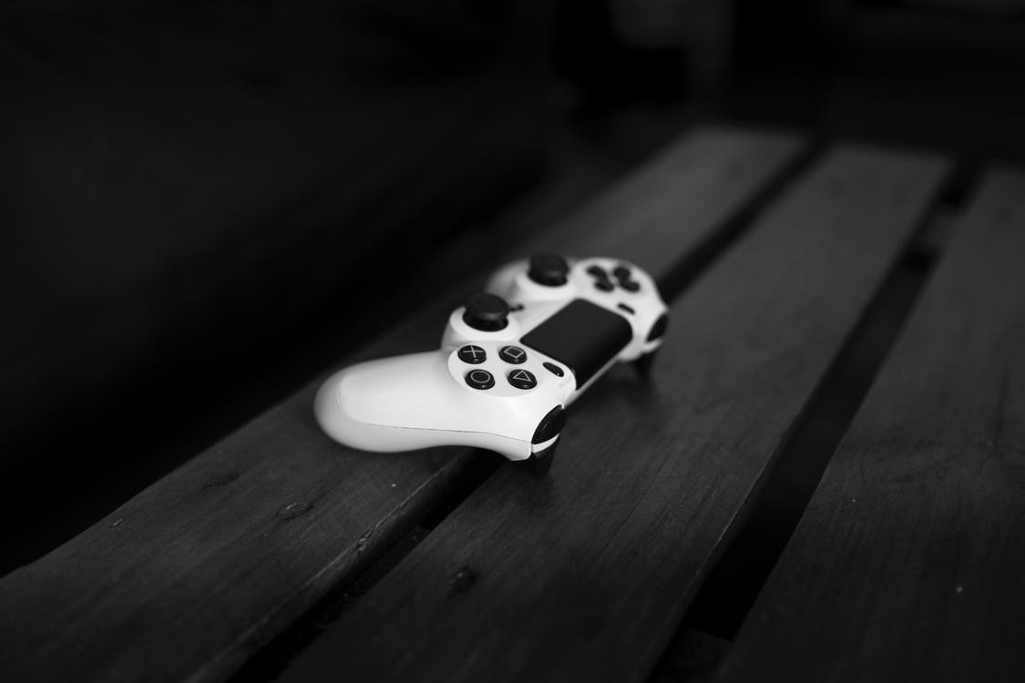 White Sony Dualshock 4 Controller on Black Wood Surface