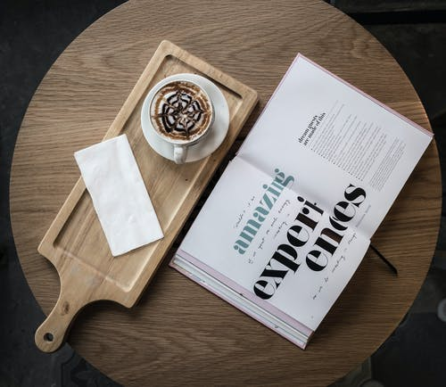 Top view of cup of cappuccino garnished with chocolate topping served with saucer and napkin on wooden board placed on cafe round table with open book with amazing experiences title on pages