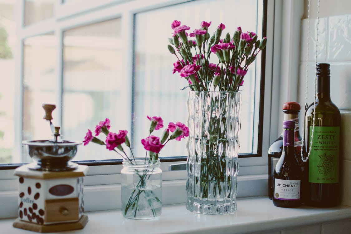 Potted Pink Petaled Flowers Near Bottles Beside Window