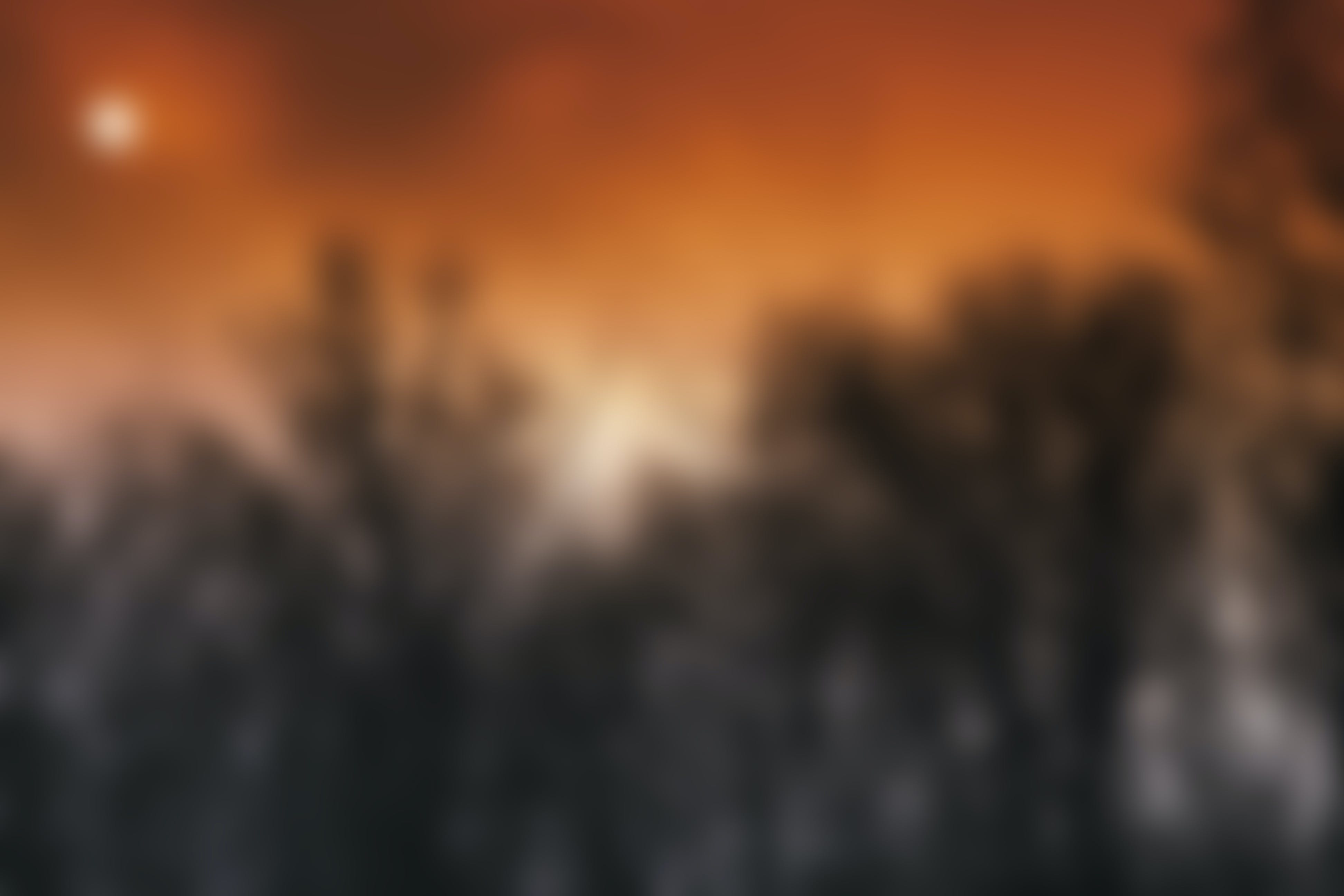 This is a blurred photo of black trees in the foreground and a red sunset in the background. The sun is covered by some clouds.