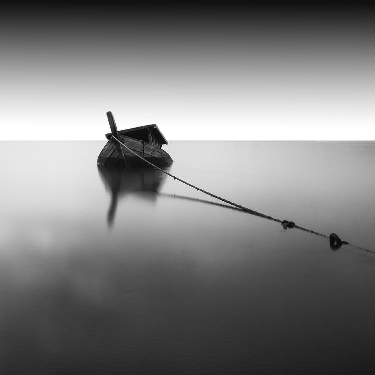 Grayscale Photography of Boat on Calm Water