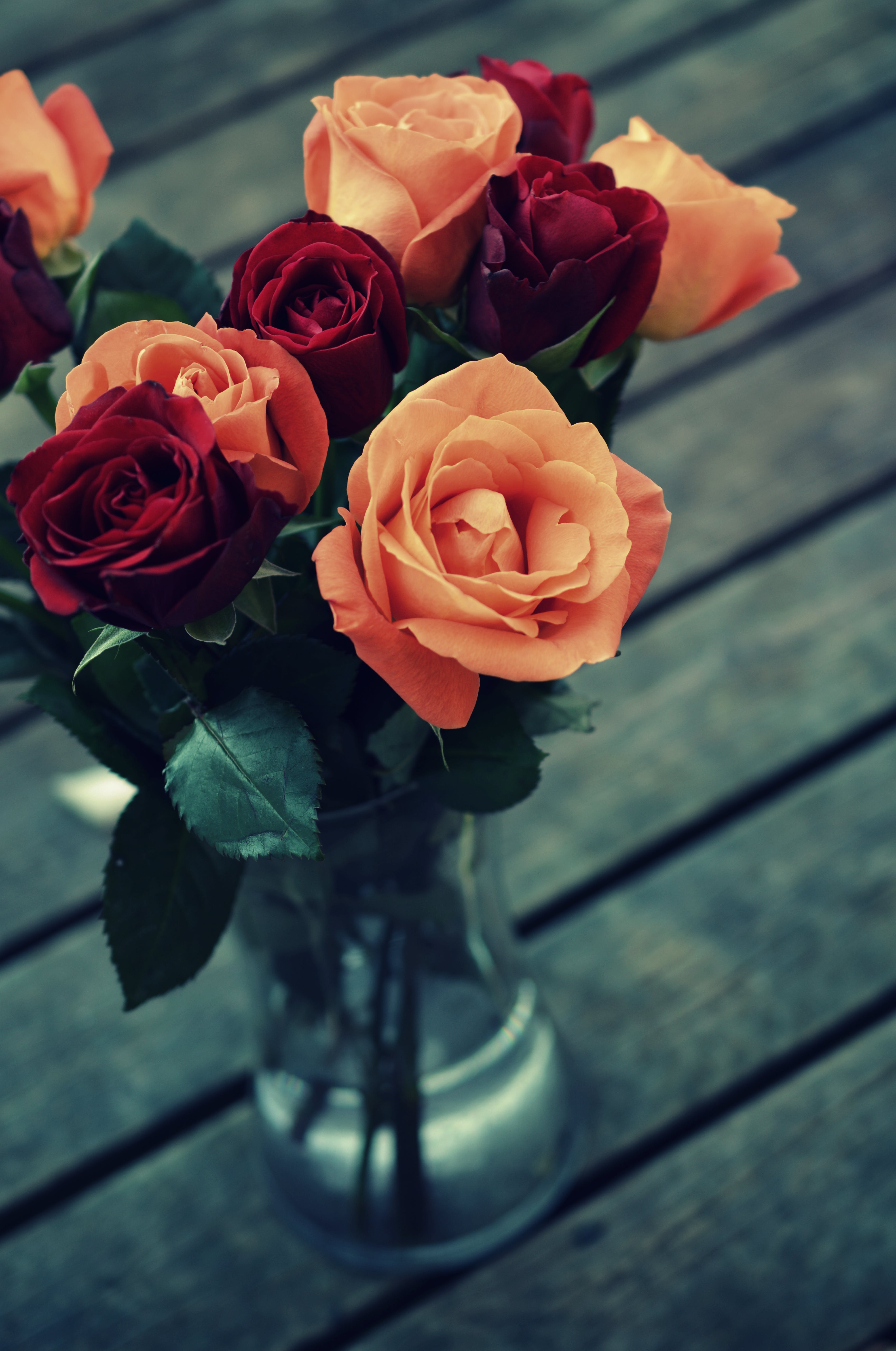 Red and Orange Roses in Clear Glass Vase
