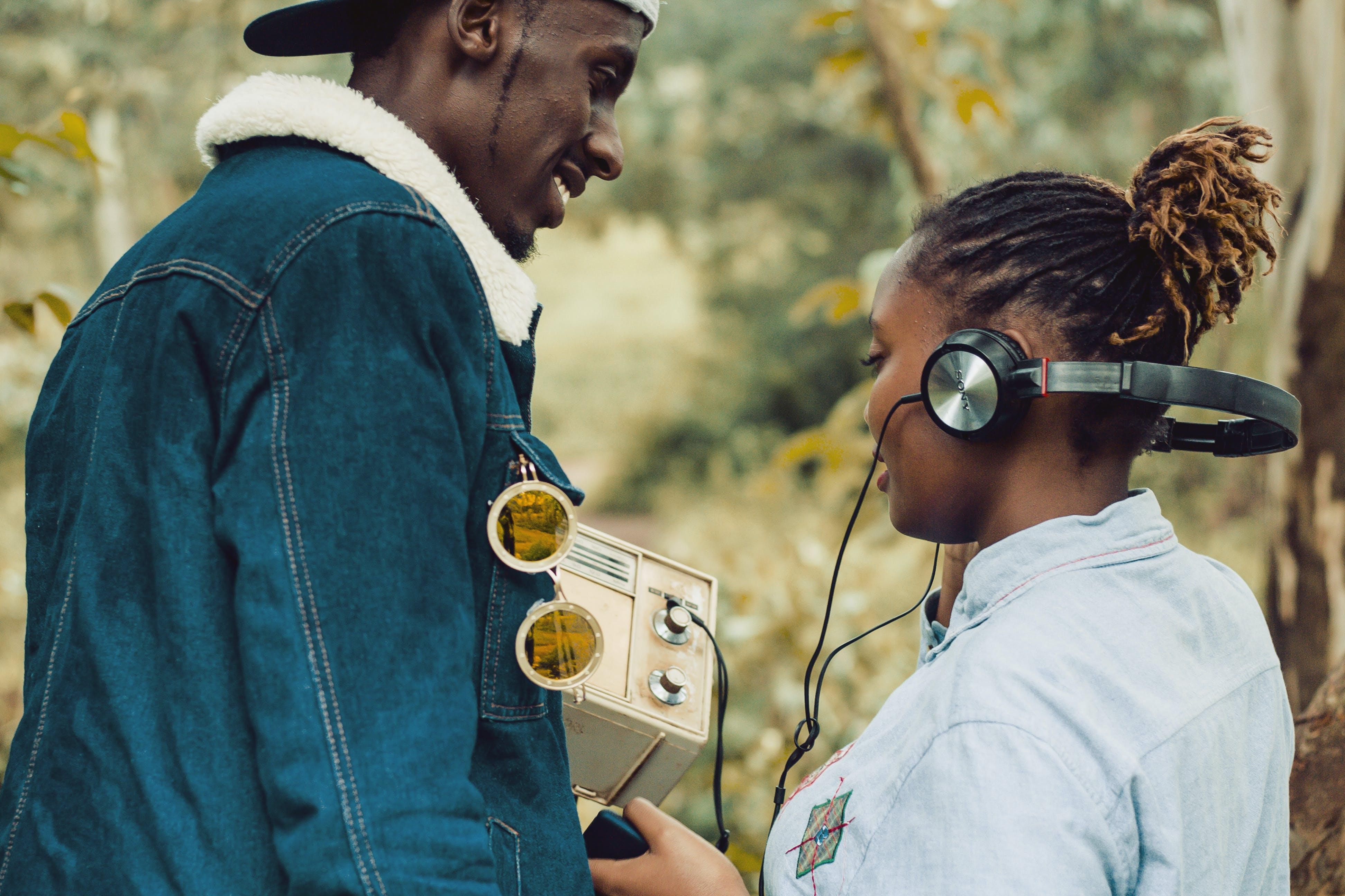Woman Wearing Headphones Standing Beside Man