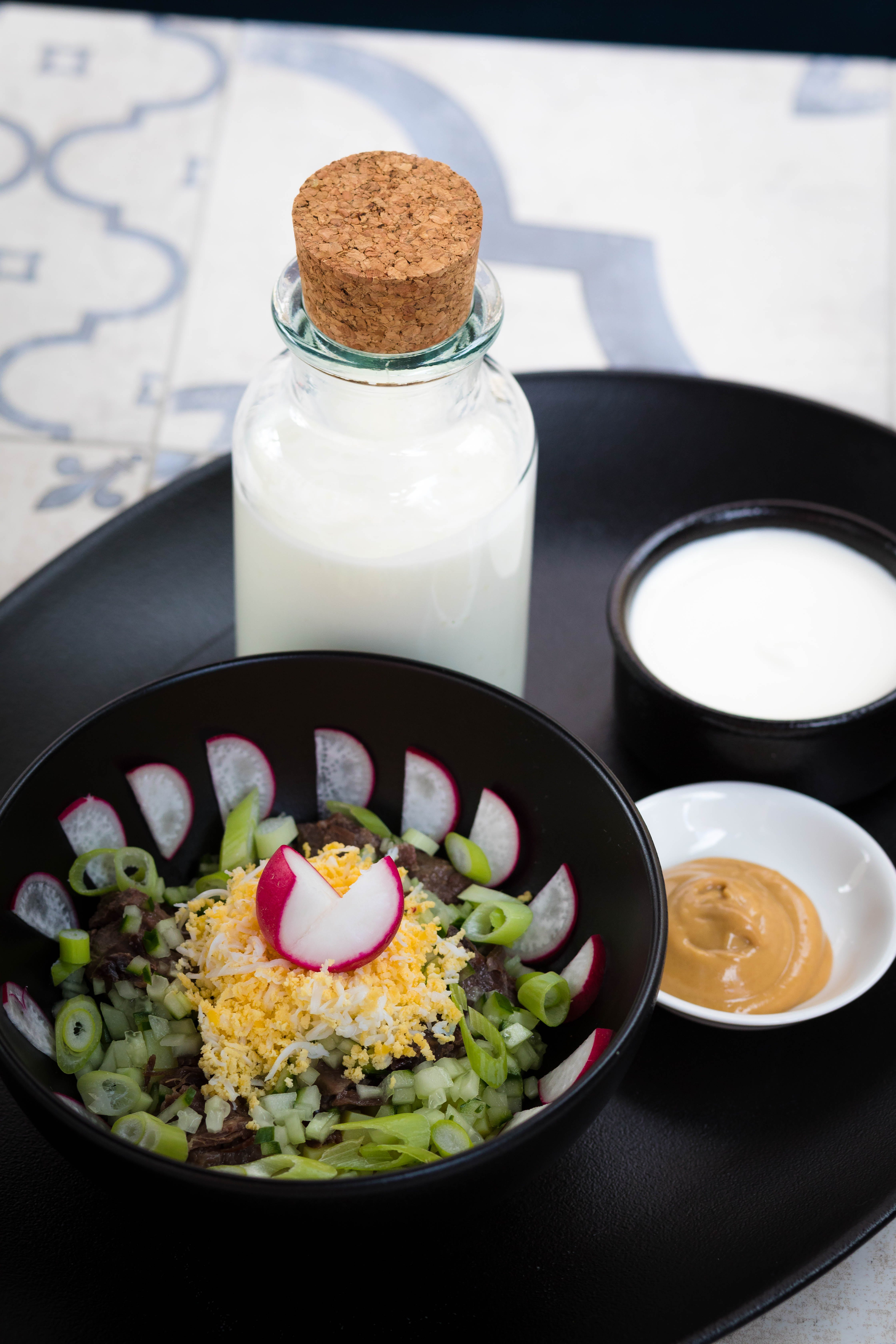 Vegetable Salad Beside Milk Bottle and Brown Sauce Dip on Round Black Tray