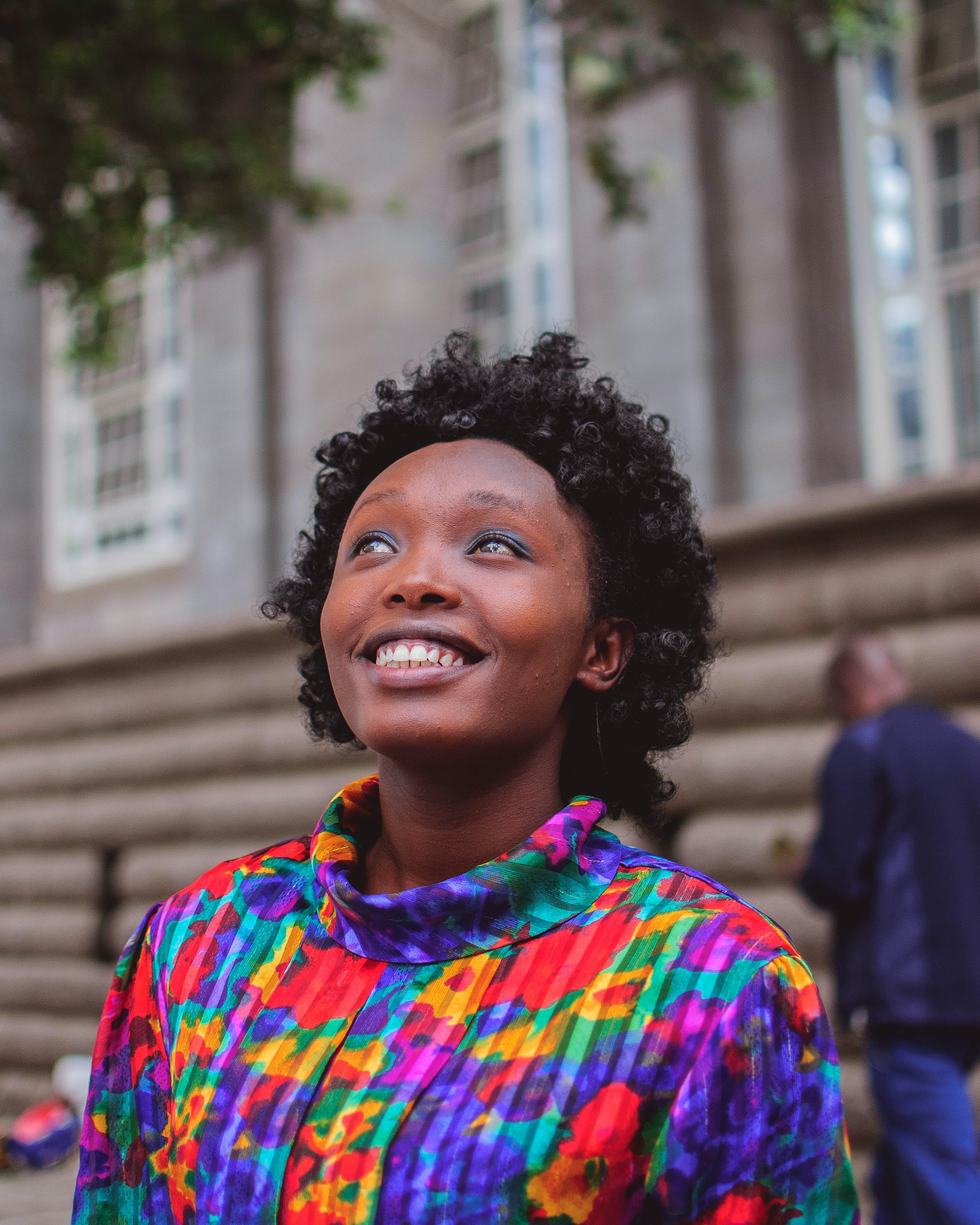 Woman Wearing Multicolored Top Smiling and Looking Up