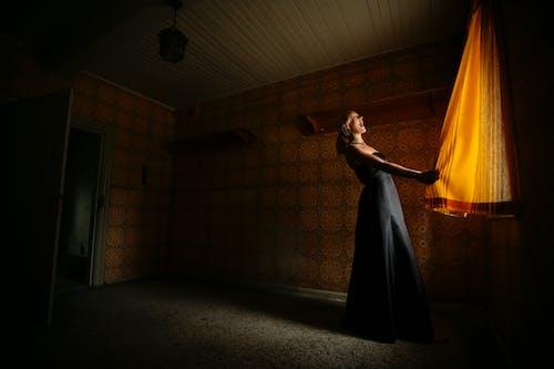 Standing Woman Wearing Black Dress Holding Curtain