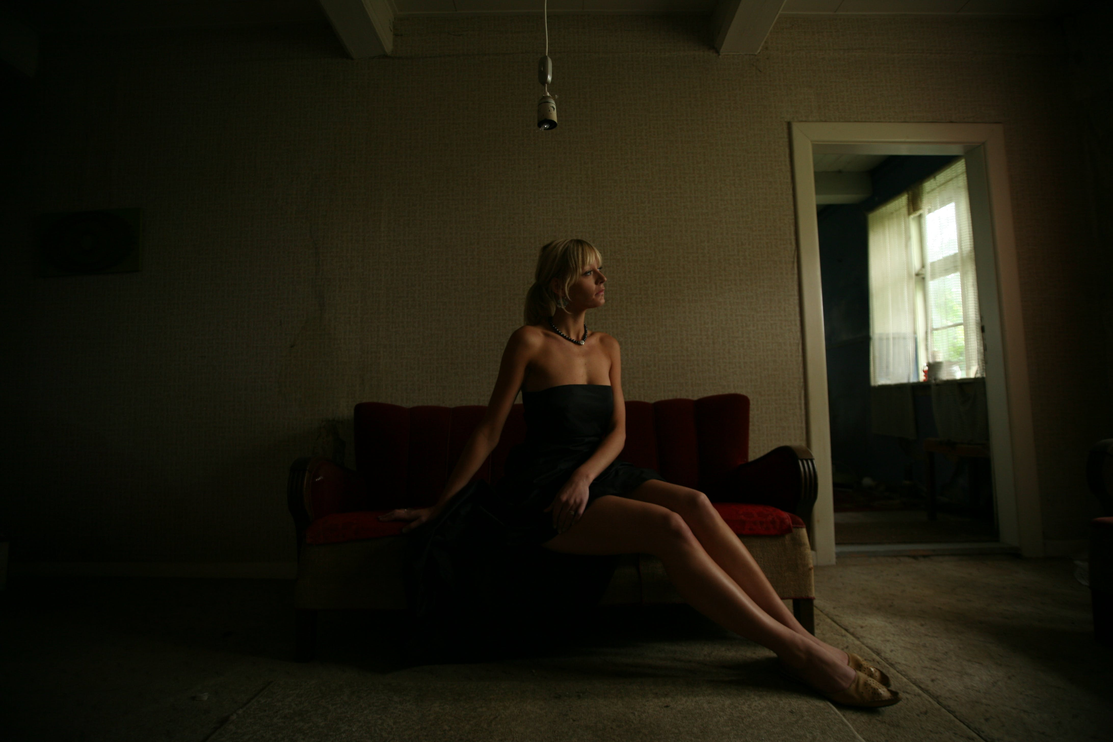 Woman Sitting on Red Sofa Beside the Door
