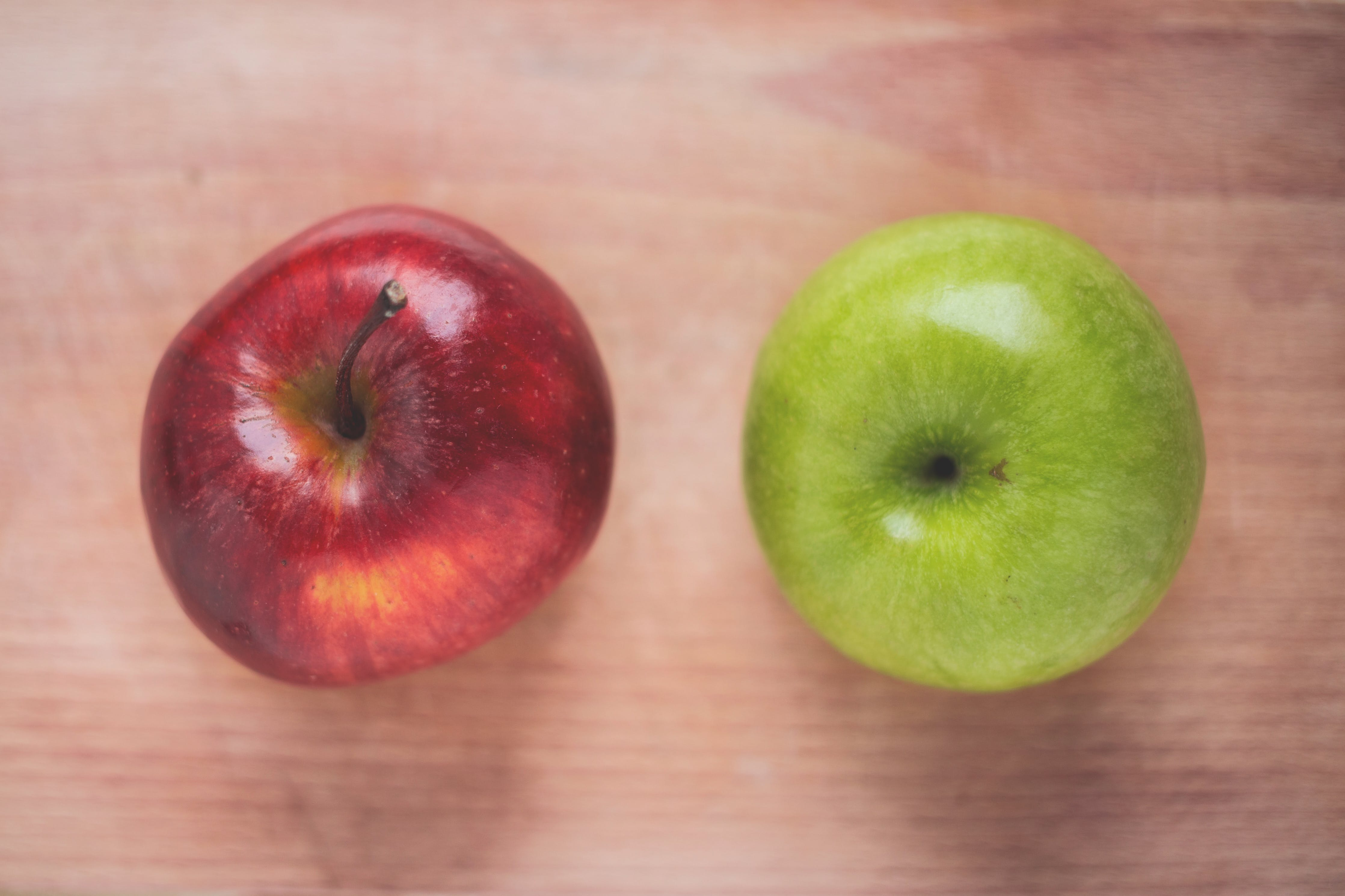 Two Red and Green Apple Fruits on Brown Surface