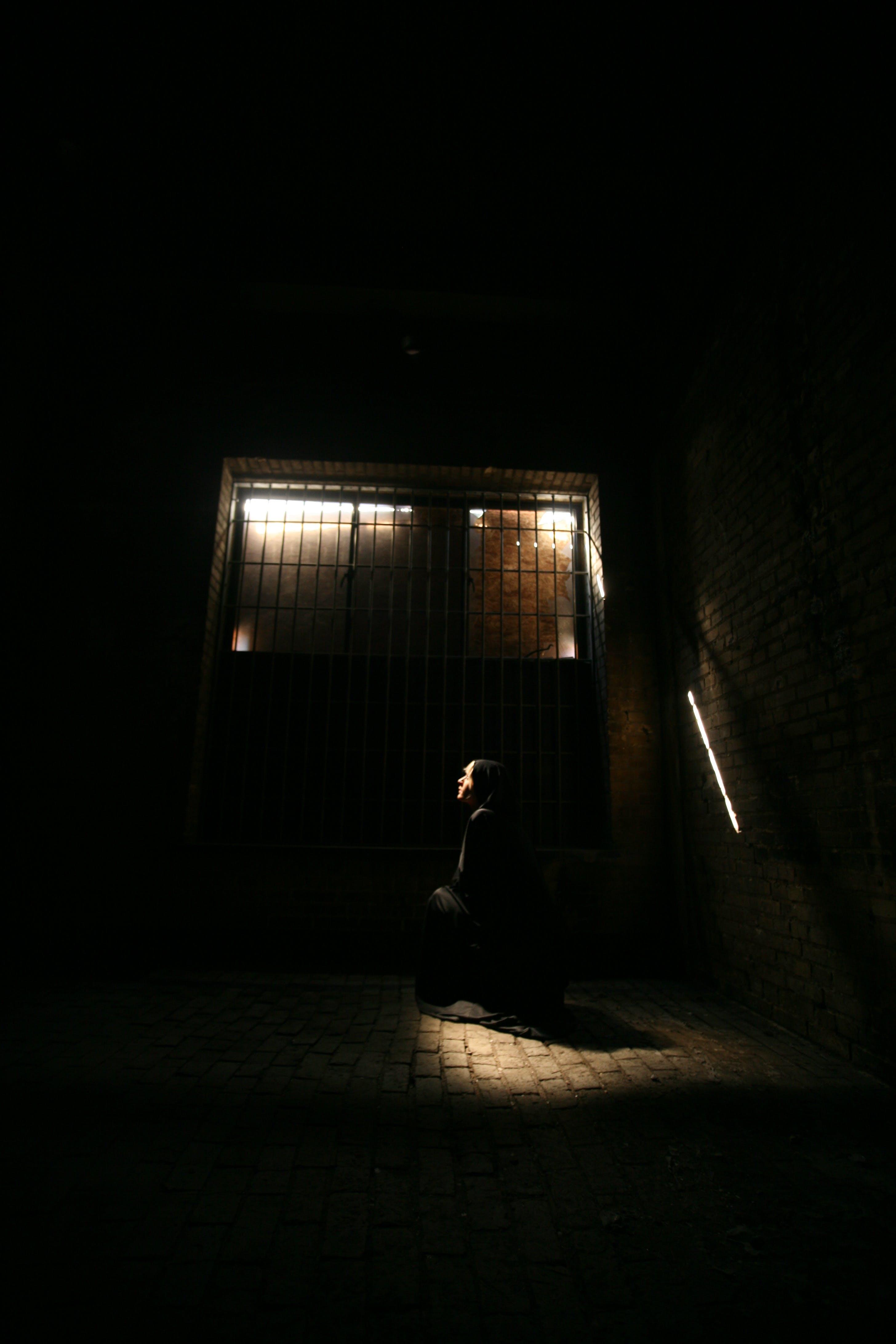 Person Sitting Near Brown Concrete Wall