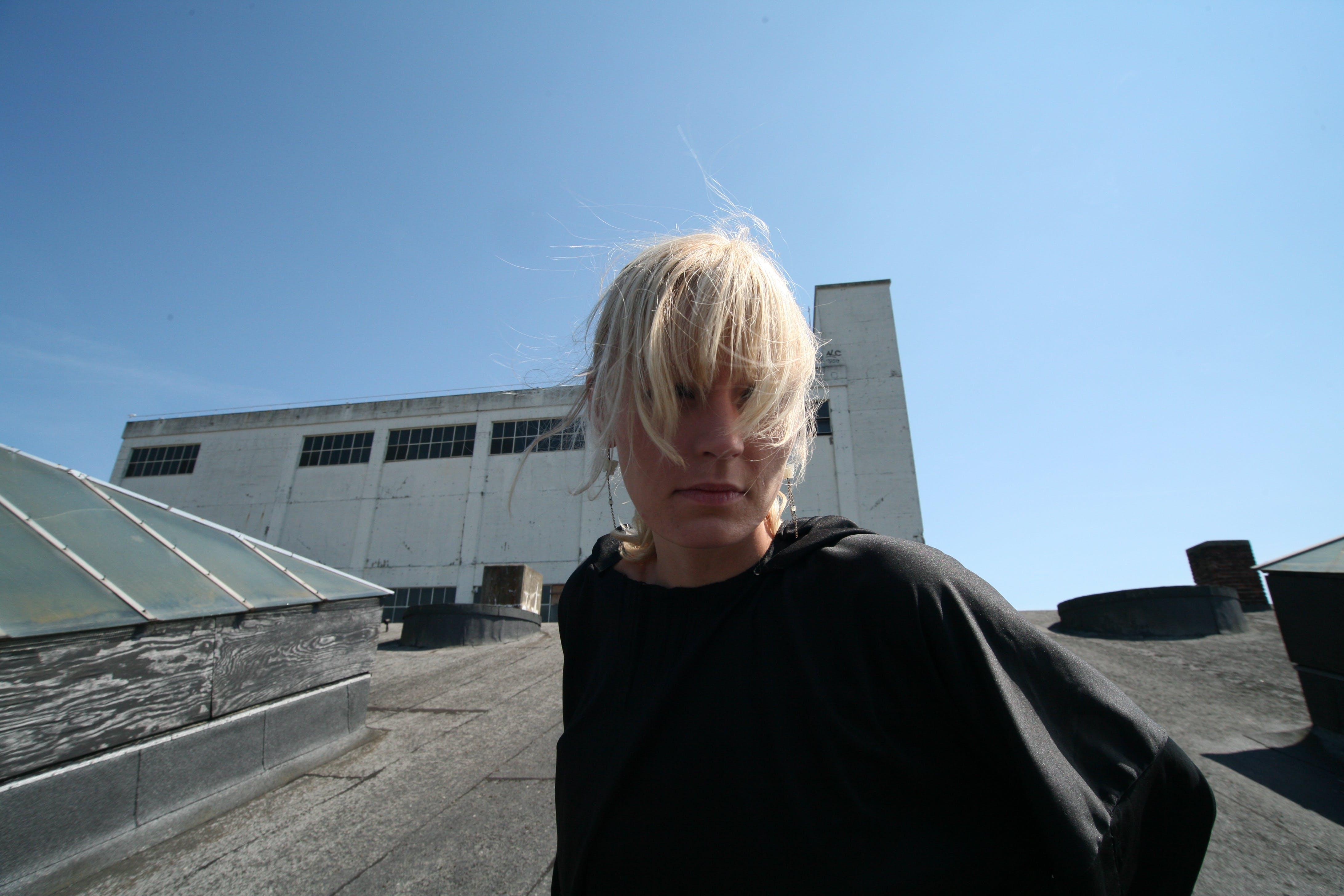 Woman Standing on Grey Concrete Pavement Under Blue Sky