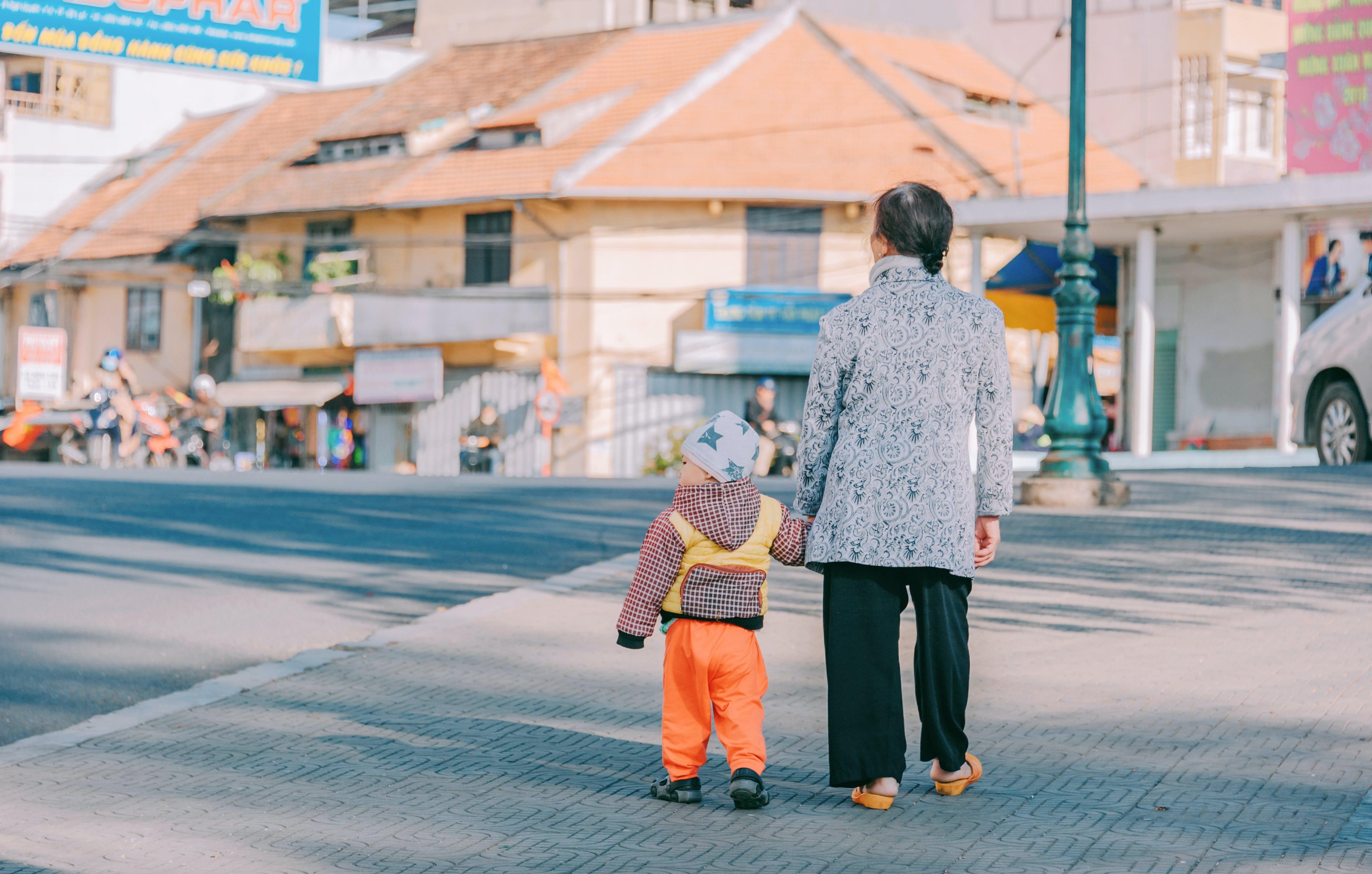 Woman and Boy Walking at Road
