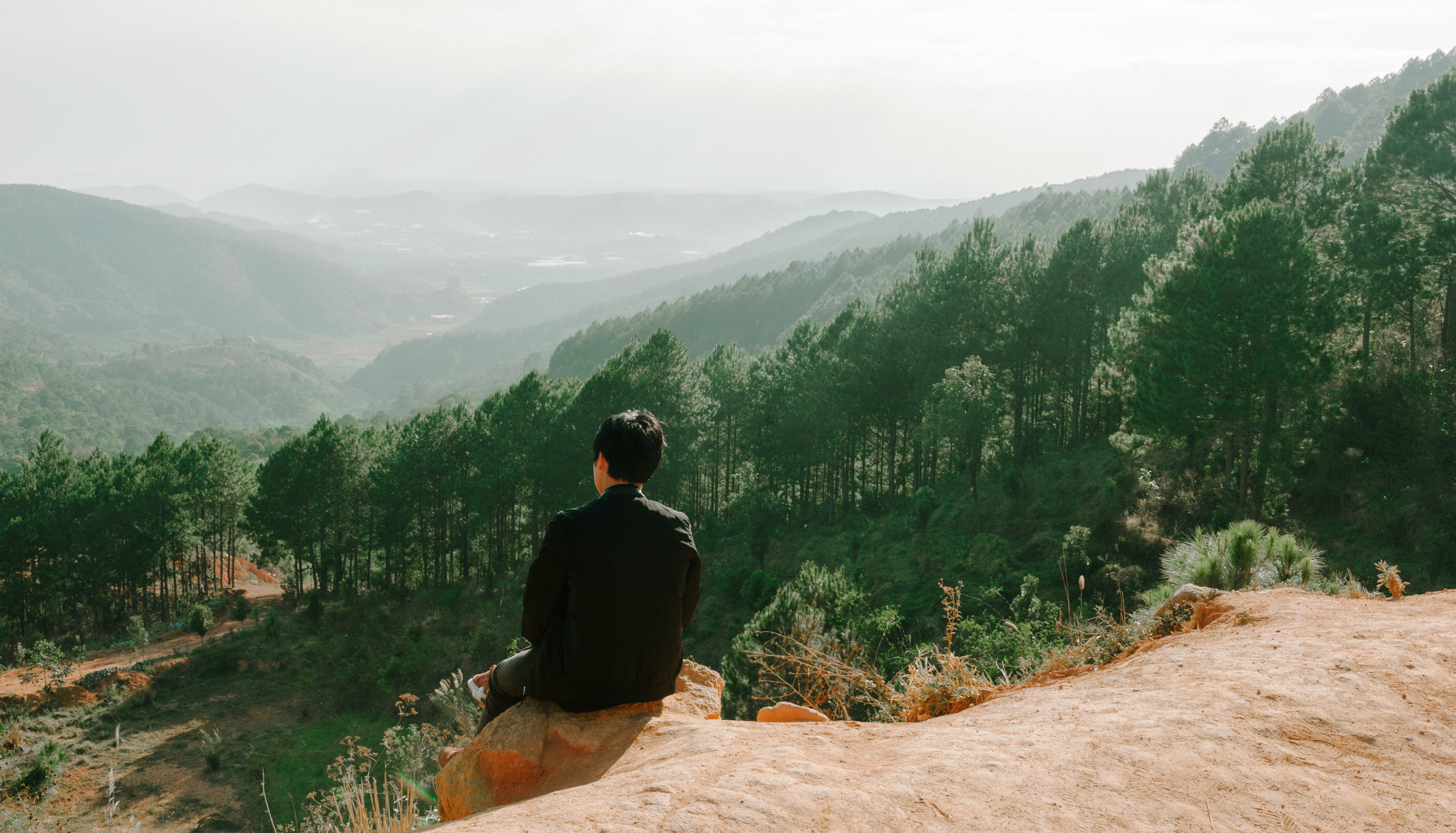 Person Sitting Near Hill Cliff