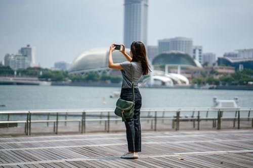 Woman Standing Taking Picture of Scenery
