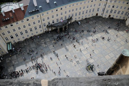 From above of travelers on square in front of aged vintage panoramic exploring sightseeing and studying place in daylight
