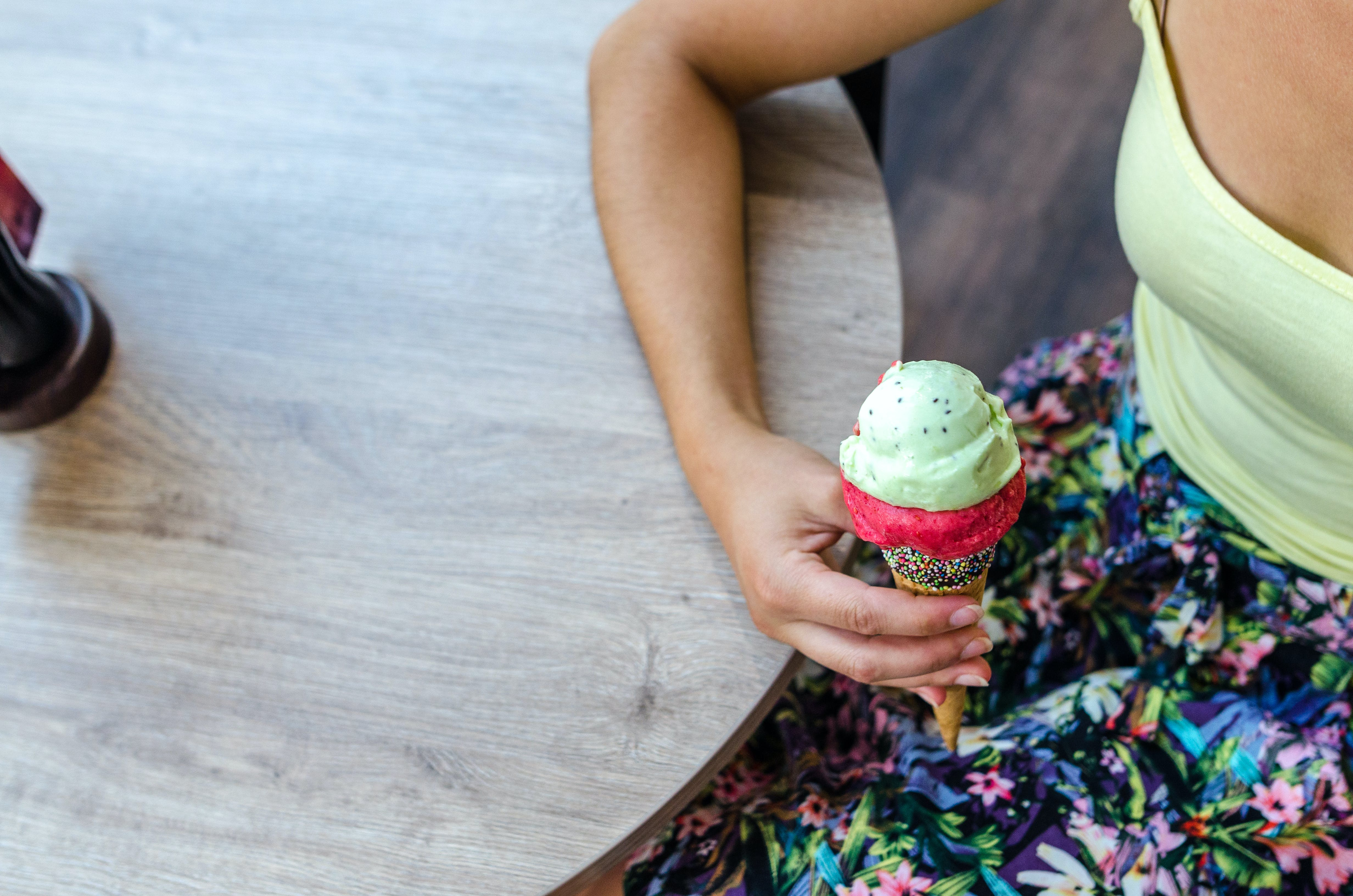 Woman Sitting While Holding Icecream Near Table