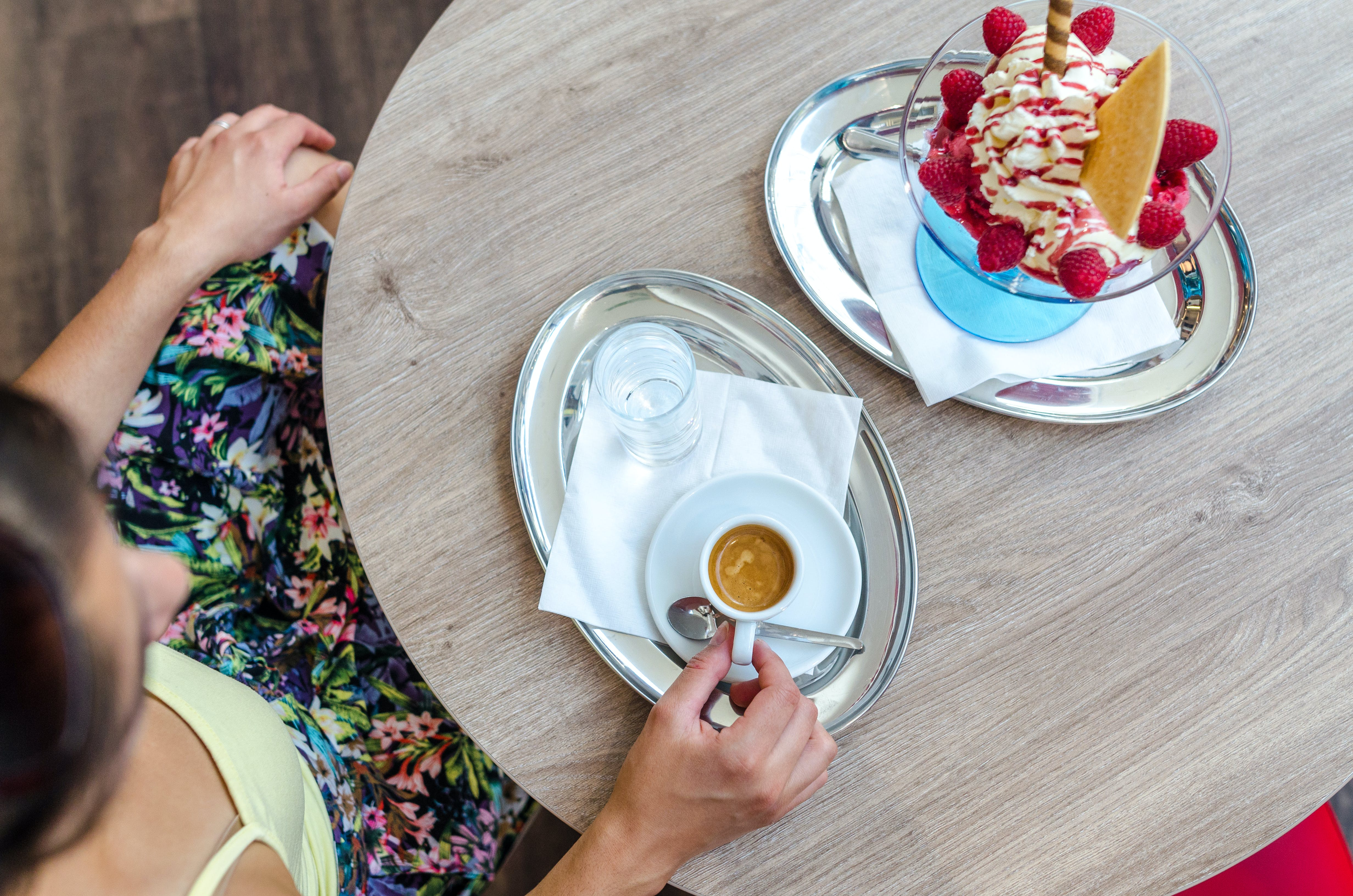 Person Sitting in Front of Wooden Table While Holding Teacup on Tray