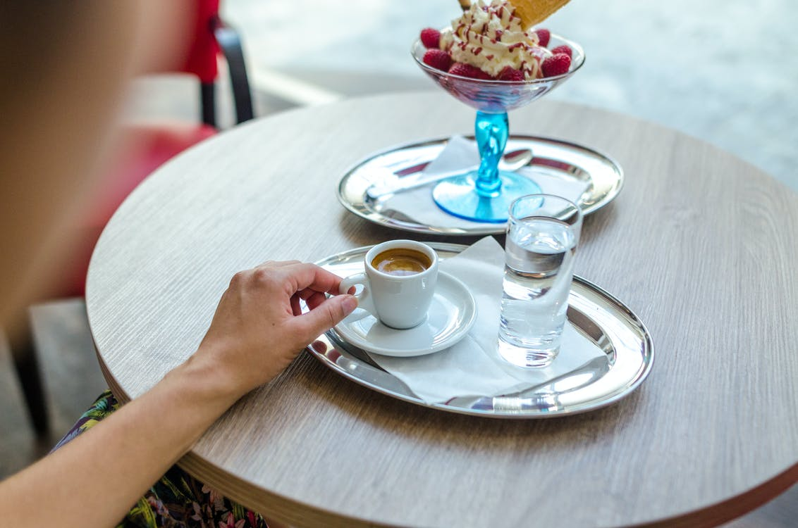Person Sitting While Holding White Teacup Filled With Brown Liquid