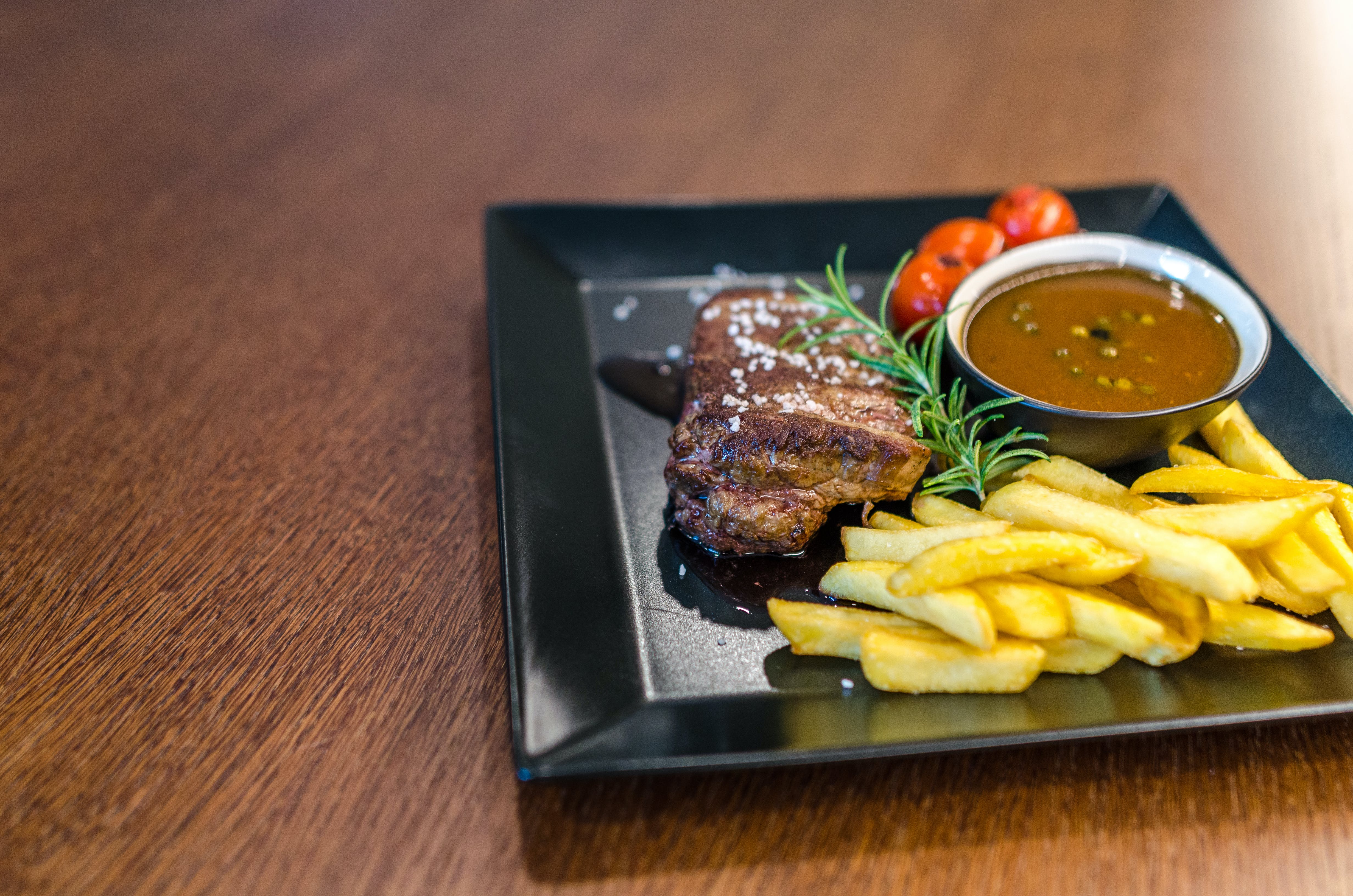 Grilled Beef With Fries and Sauce on Black Ceramic Plate