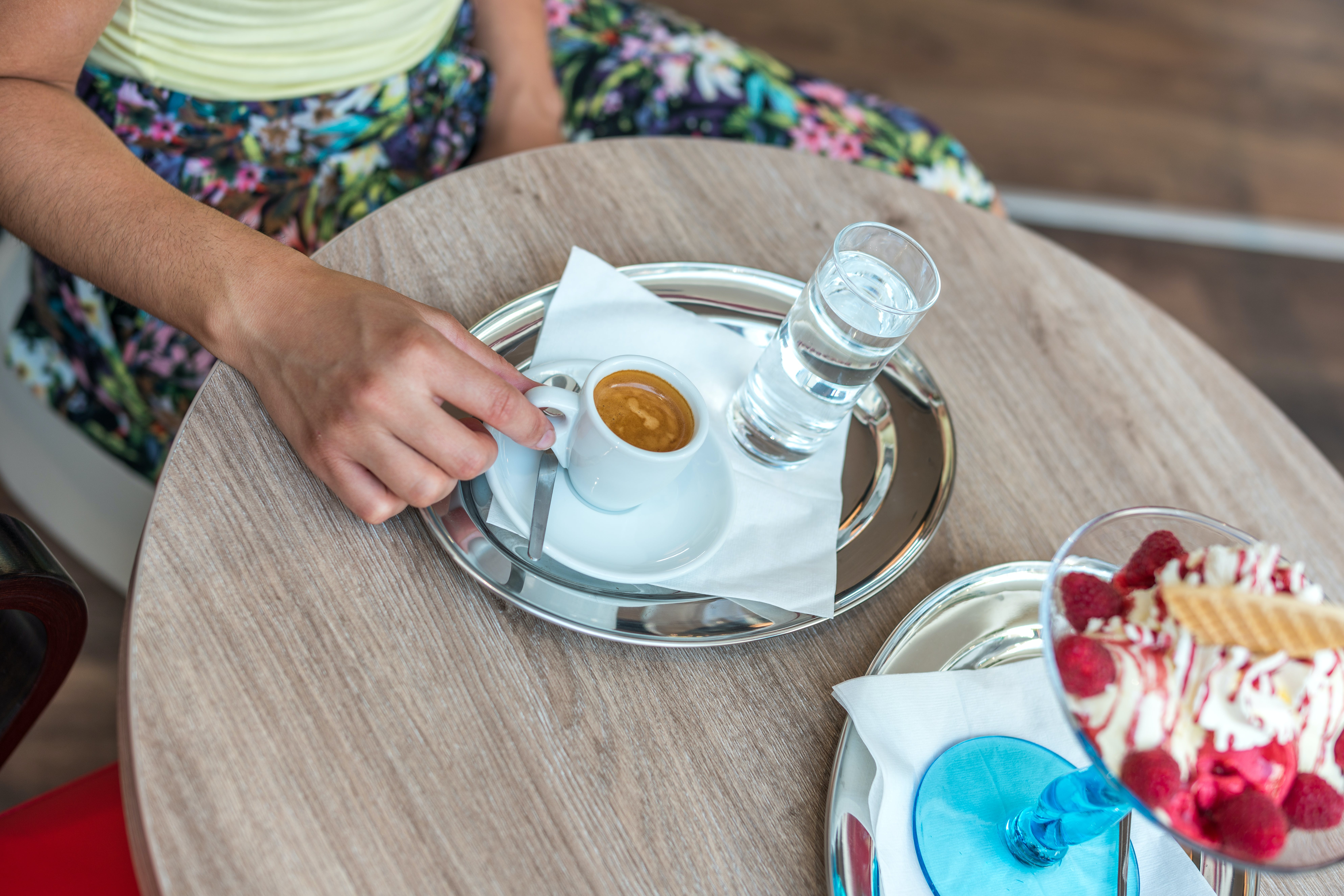 Person Sitting Beside Table While Holding Cup of Coffee