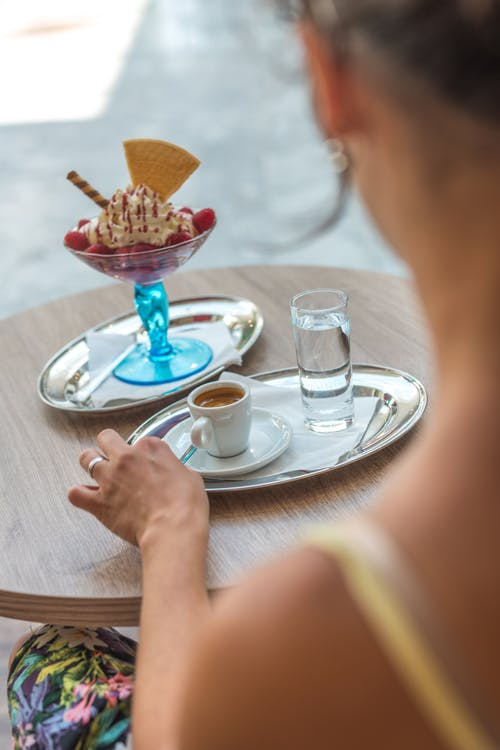 Woman Sitting on Chair While Her Left Hand Beside Coffee Mug on Gray Tray
