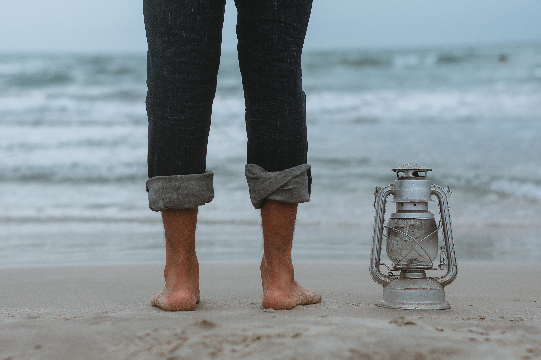 Person Standing on Shoreline Beside Gray Tubular Lantern