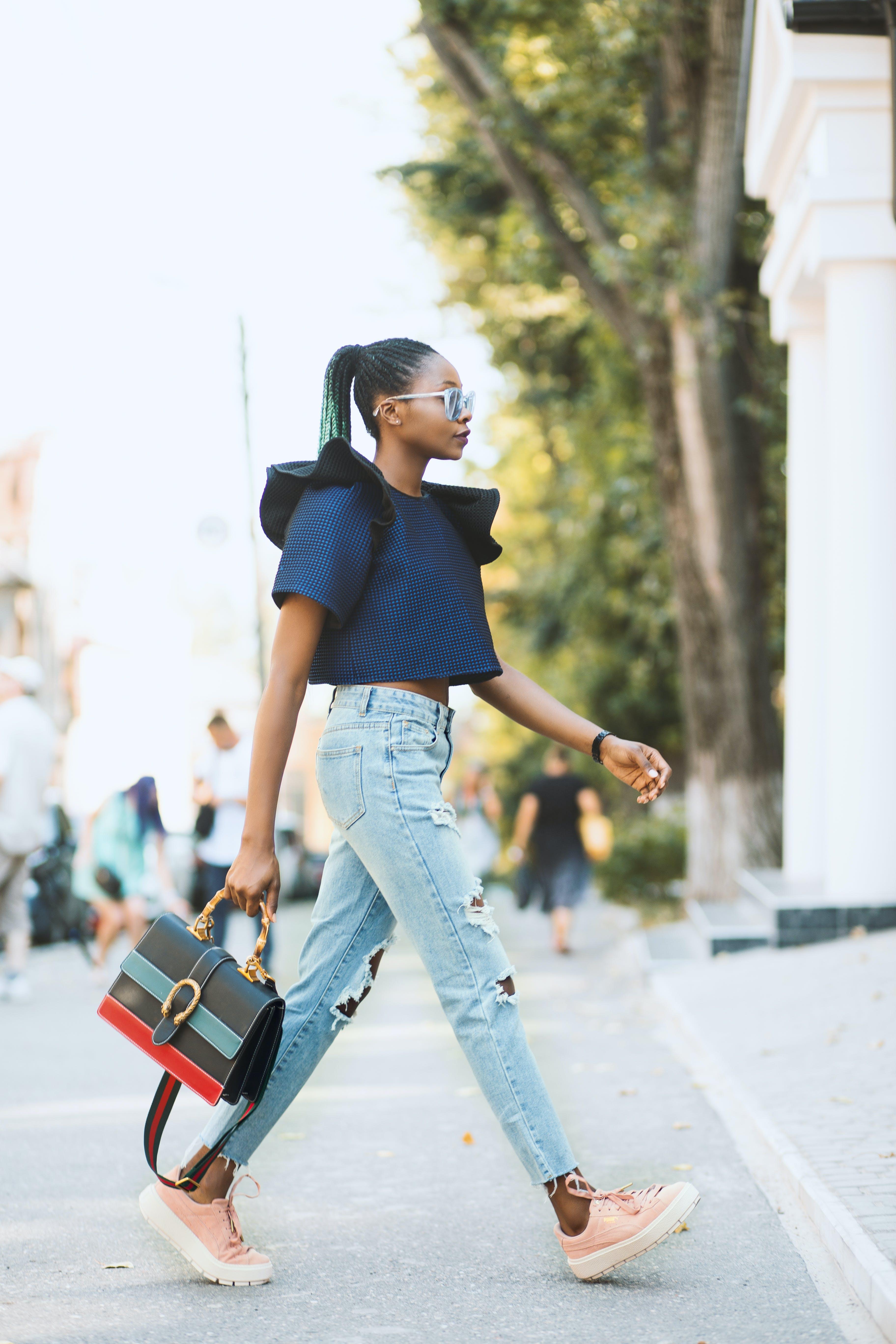 Woman in Blue Crop-top and Distressed Blue Denim Jeans Holding Black Handbag Walking on Road