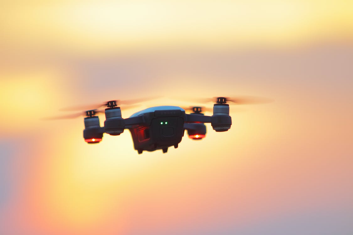 Black and Gray Dji Mavic Pro Drone Hovering at Golden Hour