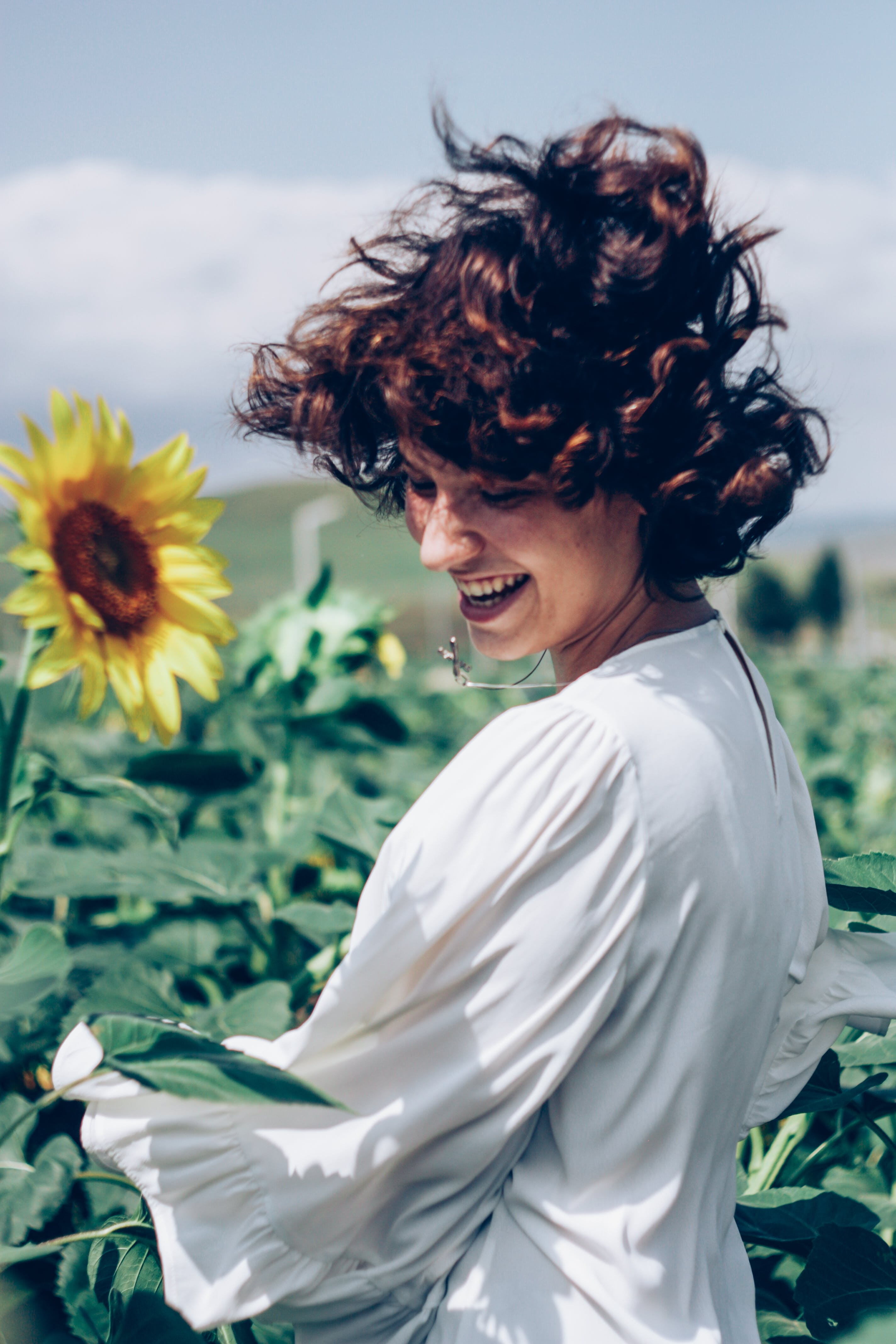 Woman Smiling at Field of Sunflowers