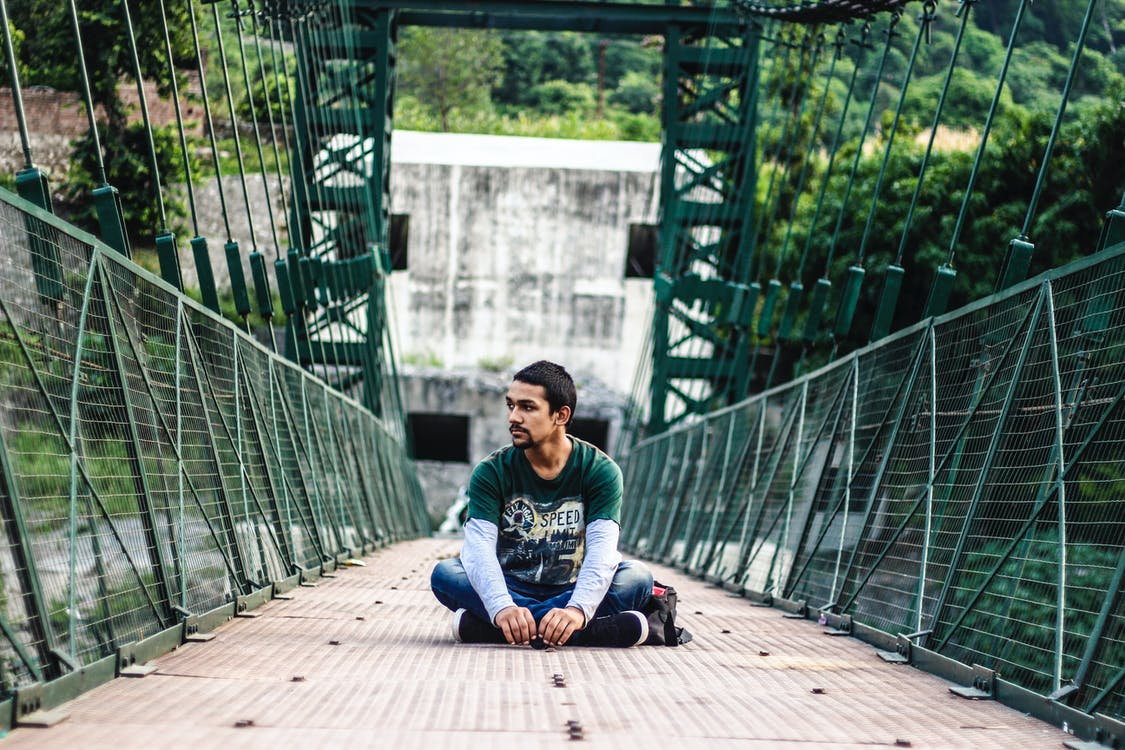Man Sitting on Bridge
