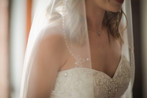 Женщина в свадебном платье и вуаль
