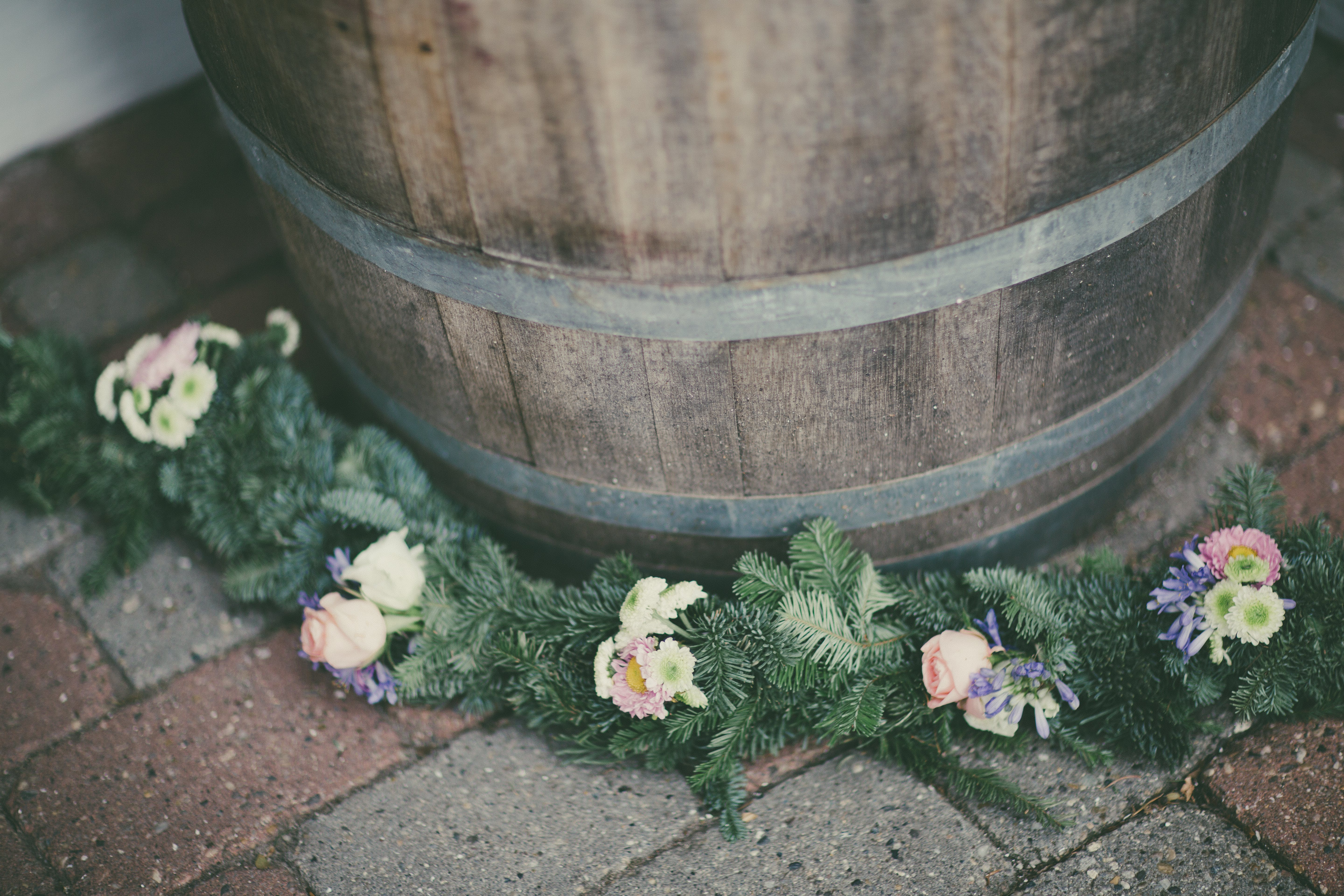 Pink and White Petaled Flowers Swag Beside Brown Wooden Barrel
