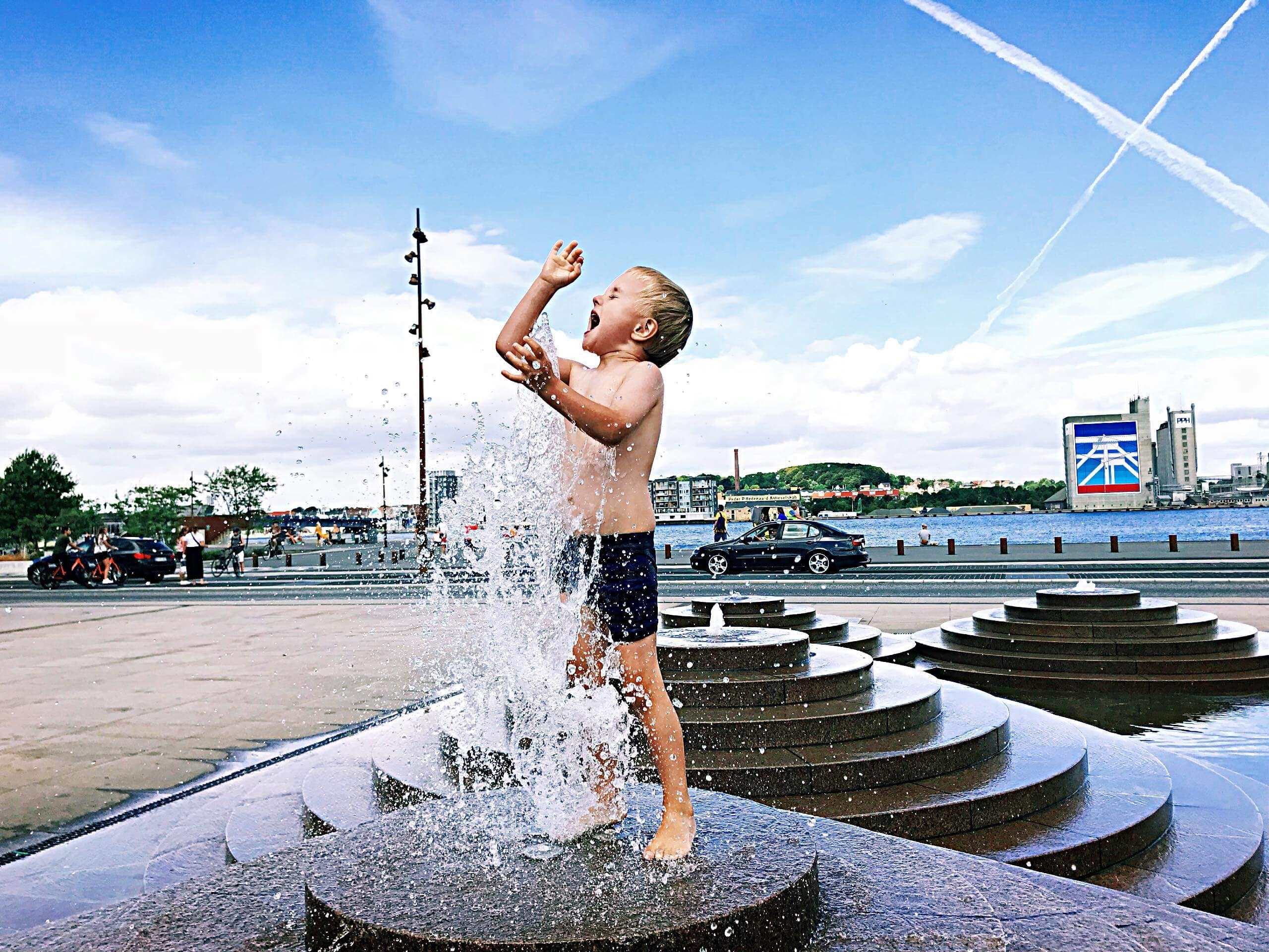 Boy Standing On Outdoor Fountain